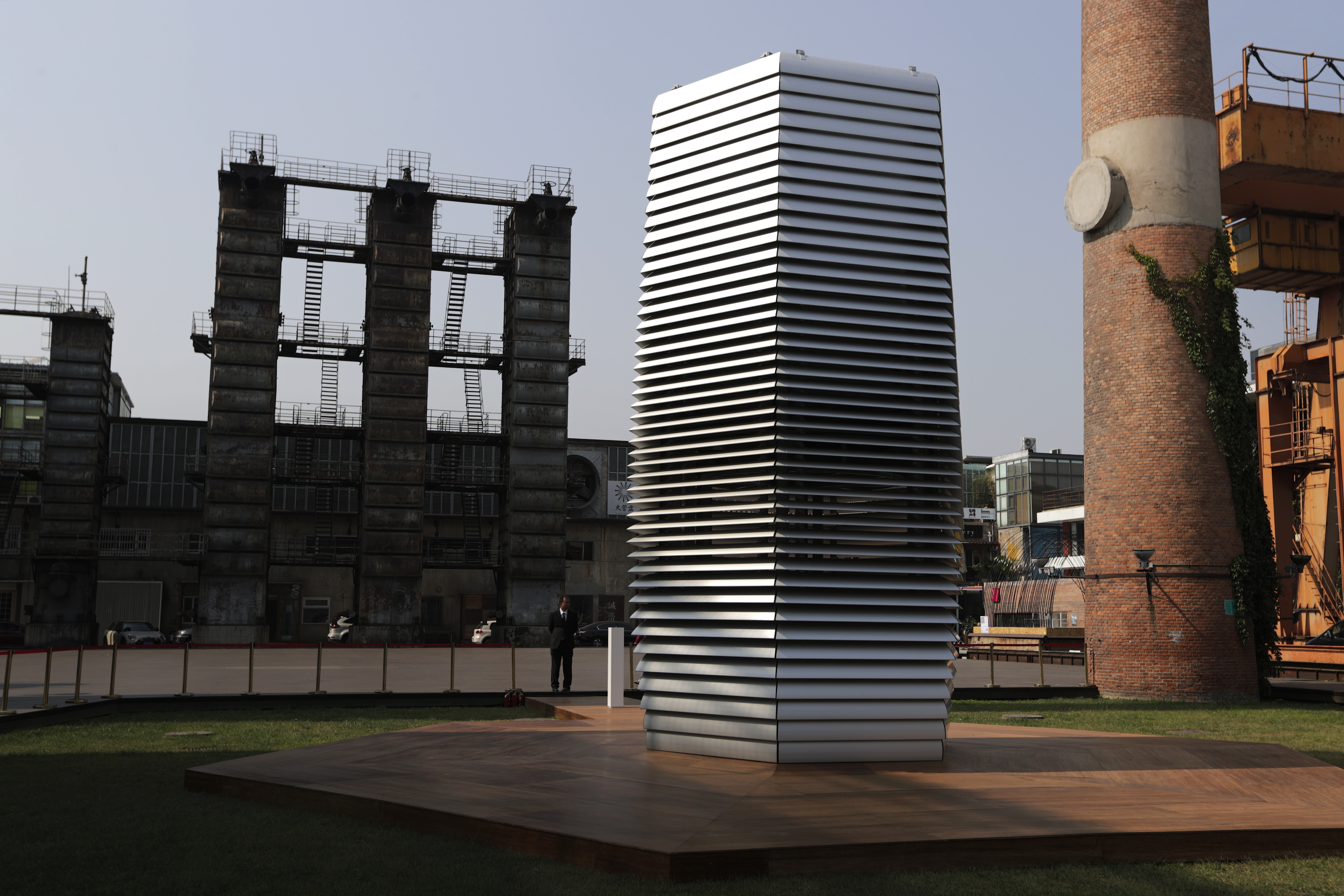 Security personnel stand near the Smog Free Tower designed by Dutch artist Daan Roosegaarde on display in between chimneys at D-751art district in Beijing, Thursday, Sept. 29, 2016. In a city where smog routinely blankets the streets and chokes off clean air, a Dutch artist has offered an eccentric solution: a 20-foot metal tower that takes in smog and purifies it like a giant outdoor vacuum cleaner. (AP Photo/Andy Wong)