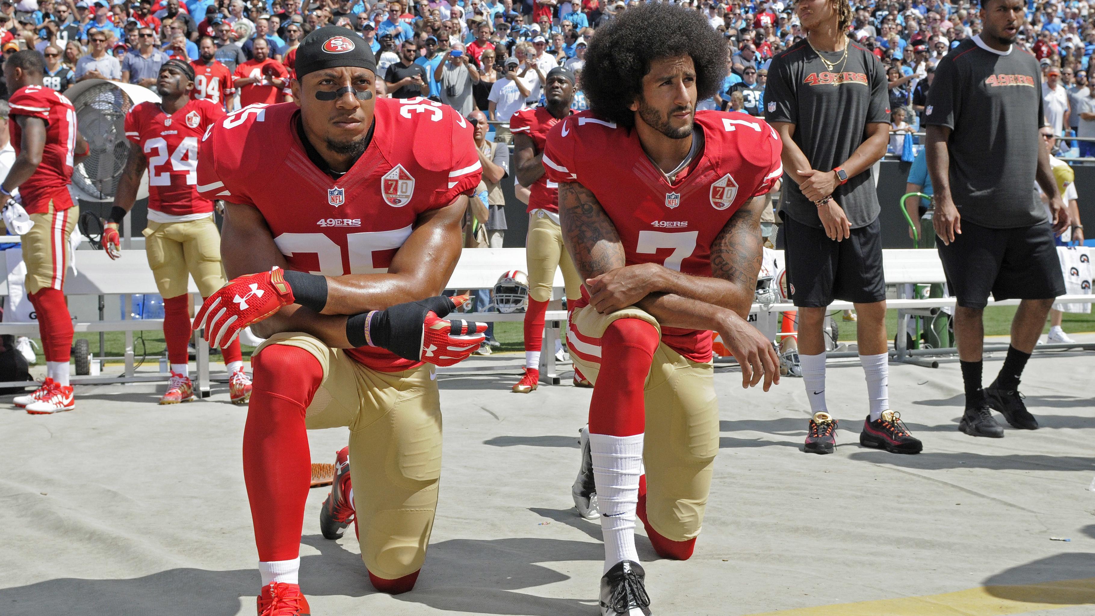 Colin Kaepernick (7) y Eric Reid, de los 49ers de San Francisco, se arrodillan durante la interpretación del himno nacional,antes de un partido de la NFL, frente a los Panthers de Carolina, el domingo 18 de septiembre de 2016 (AP Foto/Mike McCarn)