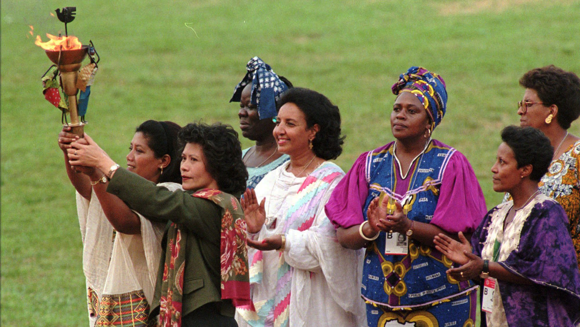 """Women representing the different cultures of the world hold the """"peace torch"""" during the opening ceremony for the Non-Governmental Organizations Forum on Women at the Olympic Stadium in Beijing Wednesday August 30, 1995. (AP Photo/Anat Givon)"""