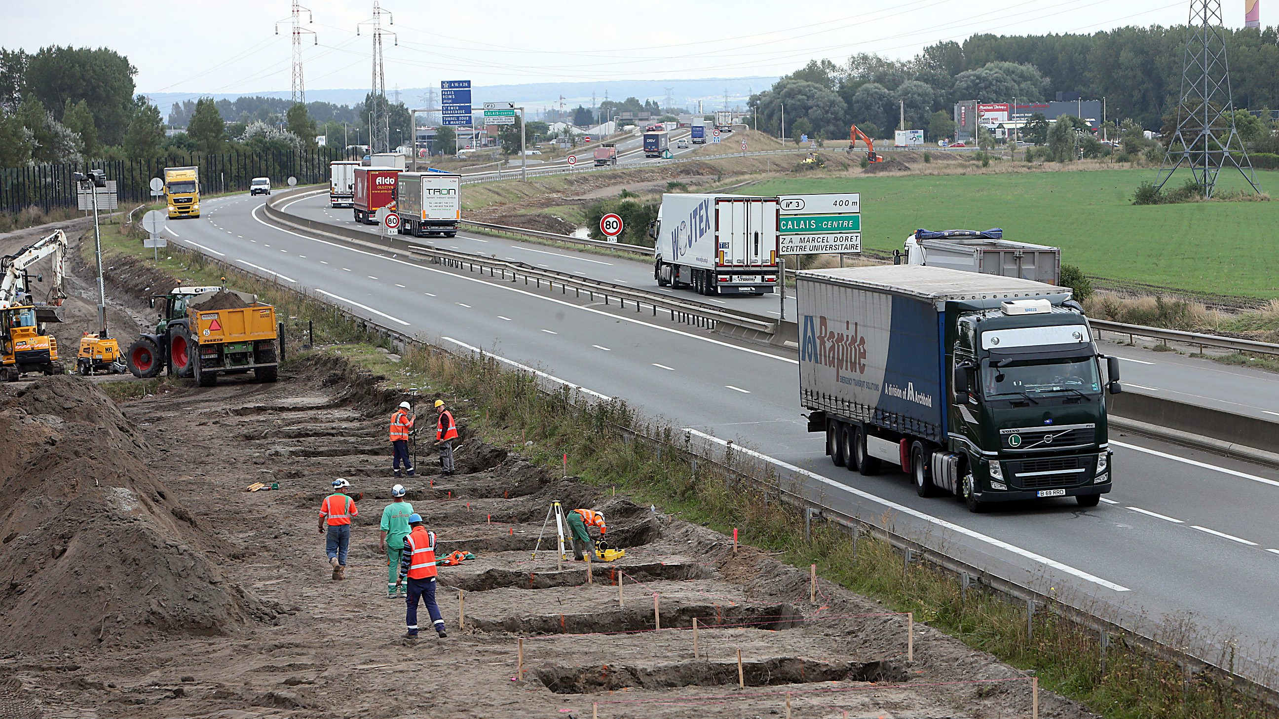 Workers begin construction of a 4-meter-high wall along the highway leading to the Calais port, outside Calais, northern France, Tuesday, Sept. 20, 2016. The kilometer-long wall being paid for by Britain, is a new barrier to try to keep migrants from crossing the English Channel. (AP Photo)