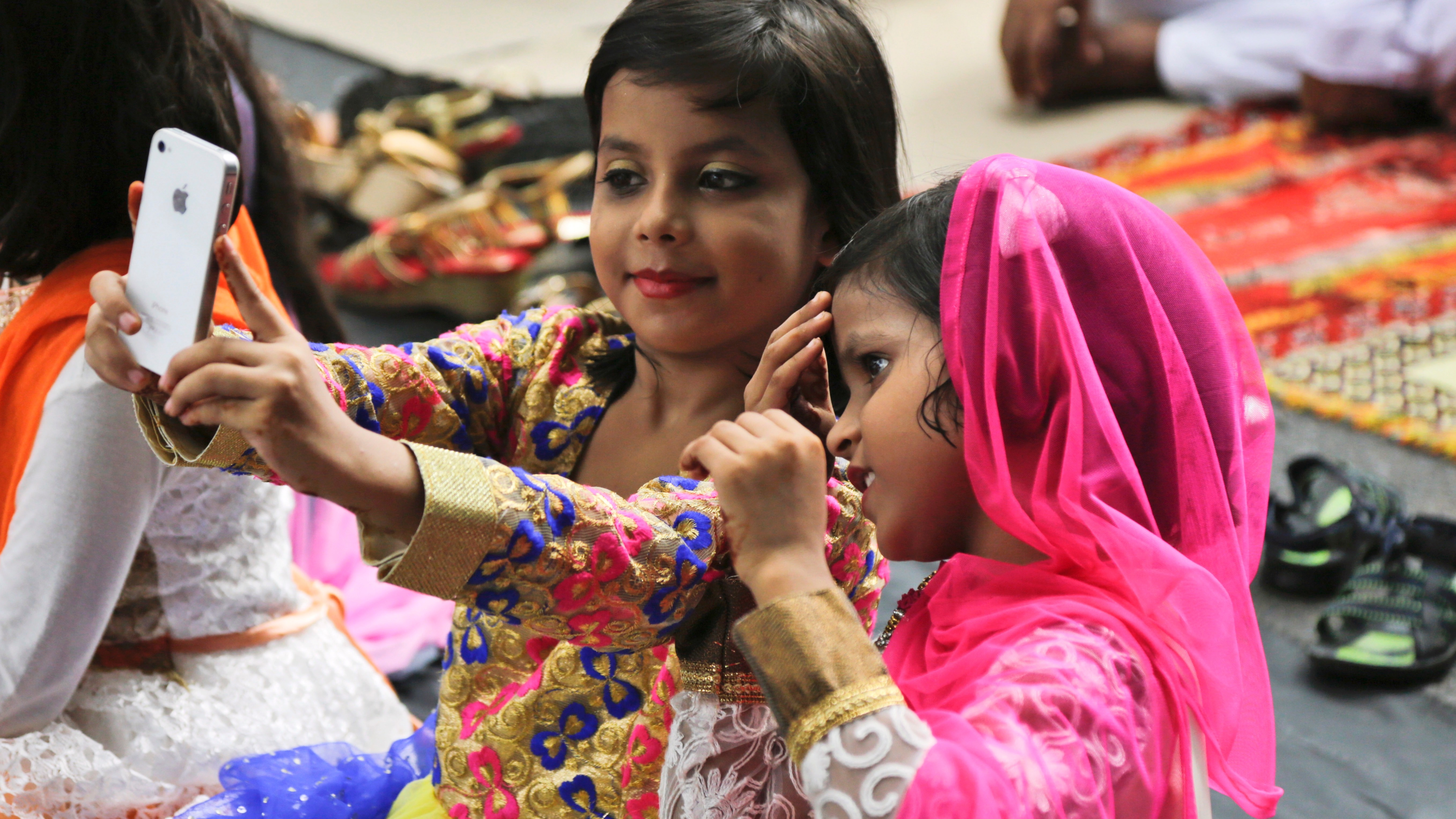 Young Indian Muslim girls take a selfie with a mobile phone as they join prayers during Eid al-Adha in Kolkata, India, Tuesday, Sept. 13, 2016. Eid al-Adha, or the festival of sacrifice, is celebrated by Muslims around the world to commemorate Prophet Ibrahim's test of faith. During the holiday, Muslims slaughter livestock and distribute part of the meat to the poor. (AP Photo/Bikas Das)