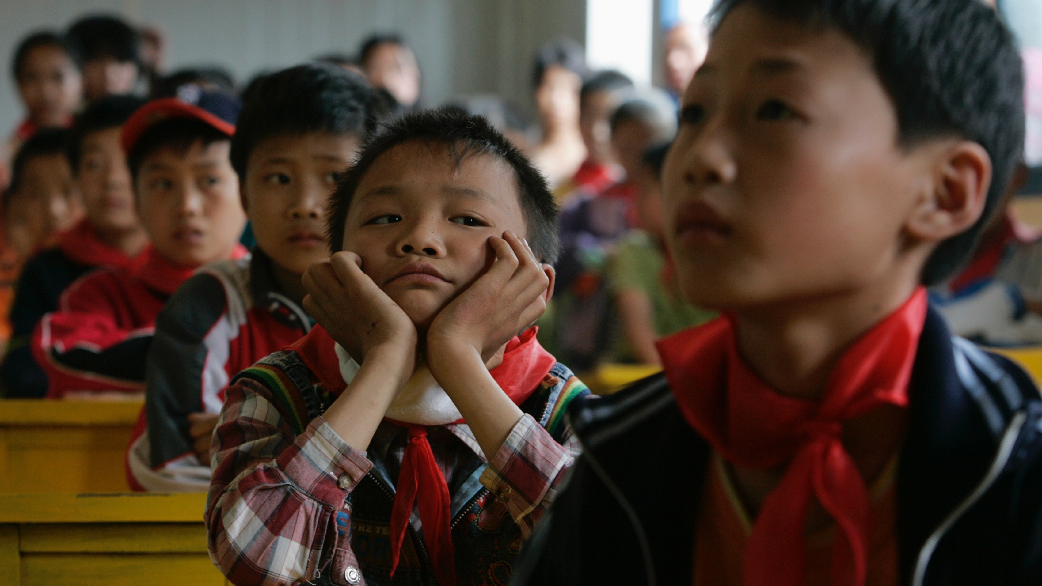 Students attend their first class in a temporary school at the township of Zundao in Mianzhu county, Sichuan Province May 21, 2008. Children returned to schools in some of China's worst hit districts on Wednesday, nine days after a massive earthquake as the country struggled to put normality back into the lives of survivors.      REUTERS/Bobby Yip  (CHINA) - RTX5ZG3