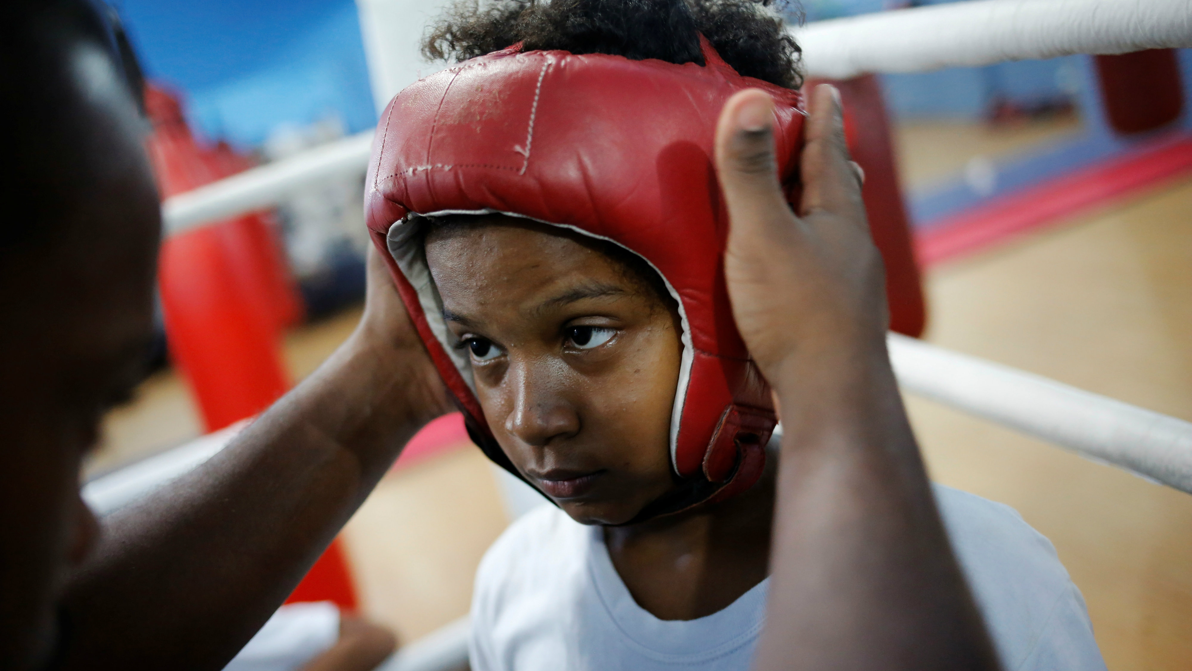 """Teacher Alan (L) puts helmet on a child during an exercise session at a boxing school, in the Mare favela of Rio de Janeiro, Brazil, June 2, 2016. REUTERS/Nacho Doce SEARCH """"NACHO BOXING"""" FOR THIS STORY. SEARCH """"THE WIDER IMAGE"""" FOR ALL STORIES"""