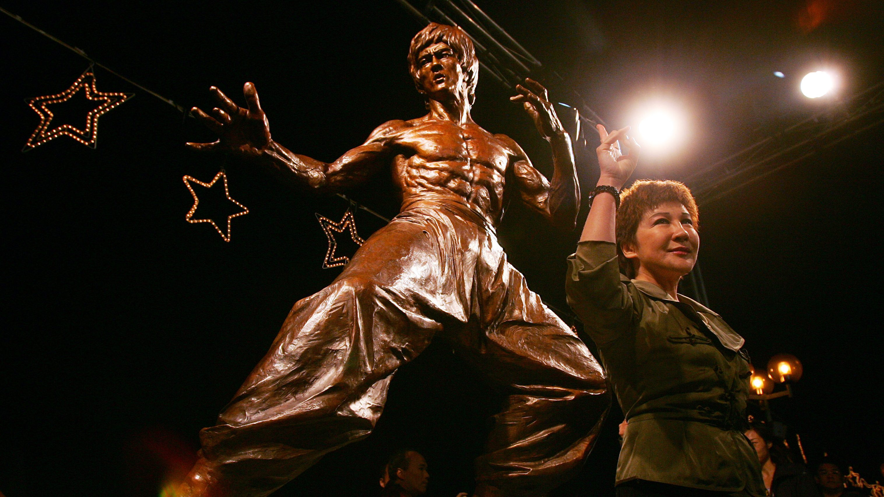 Former Hong Kong actress Betty Ting poses in front of the statue of Hong Kong martial arts movie star Bruce Lee during the statue's unveiling ceremony, on Lee's 65th birthday, in Hong Kong November 27, 2005. Lee died in Ting's home in 1973. Ting will publish a book on the story of Bruce Lee, in future.