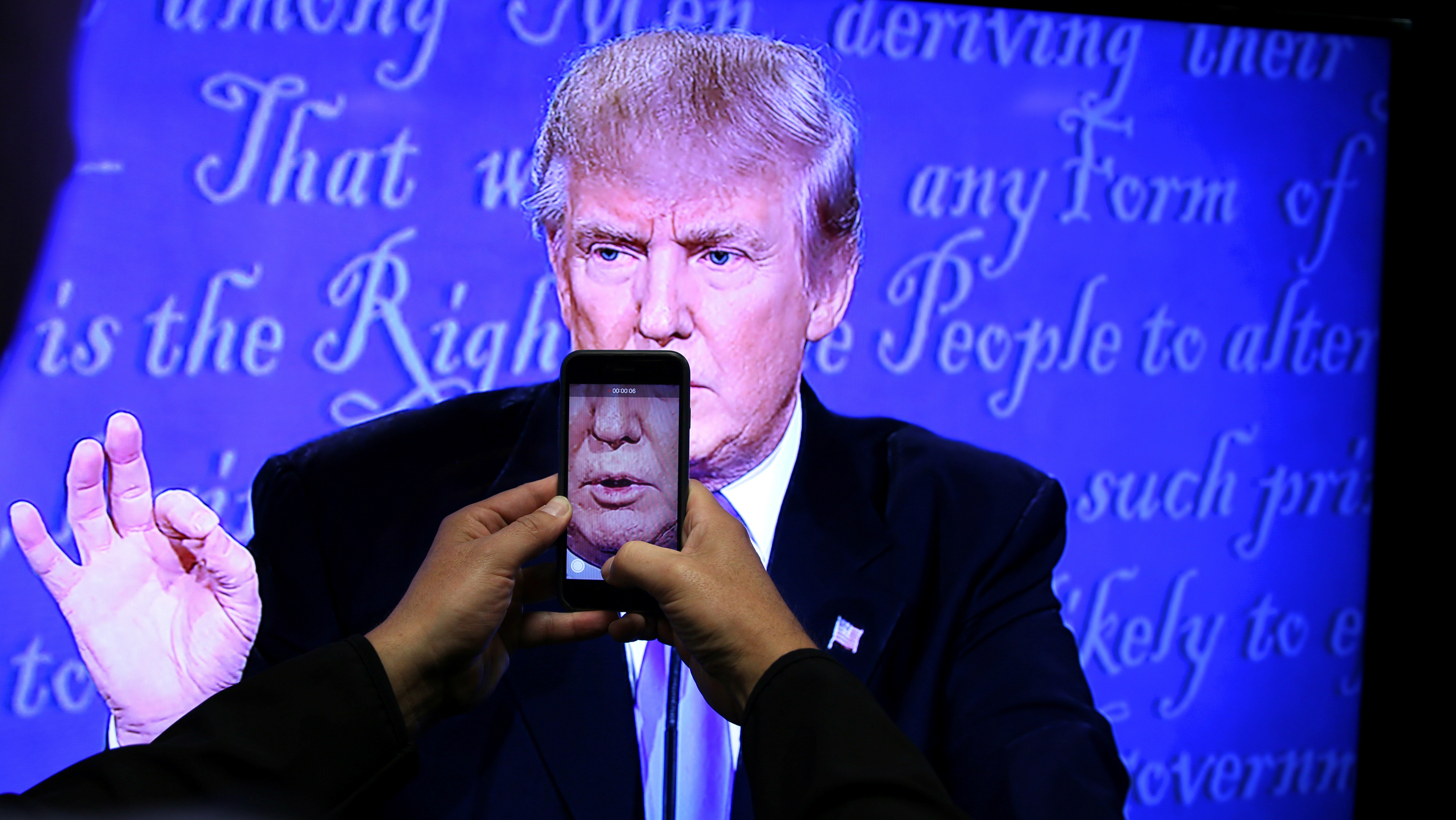 Trump speaks at a podium with a smartphone camera shot in front of his mouth