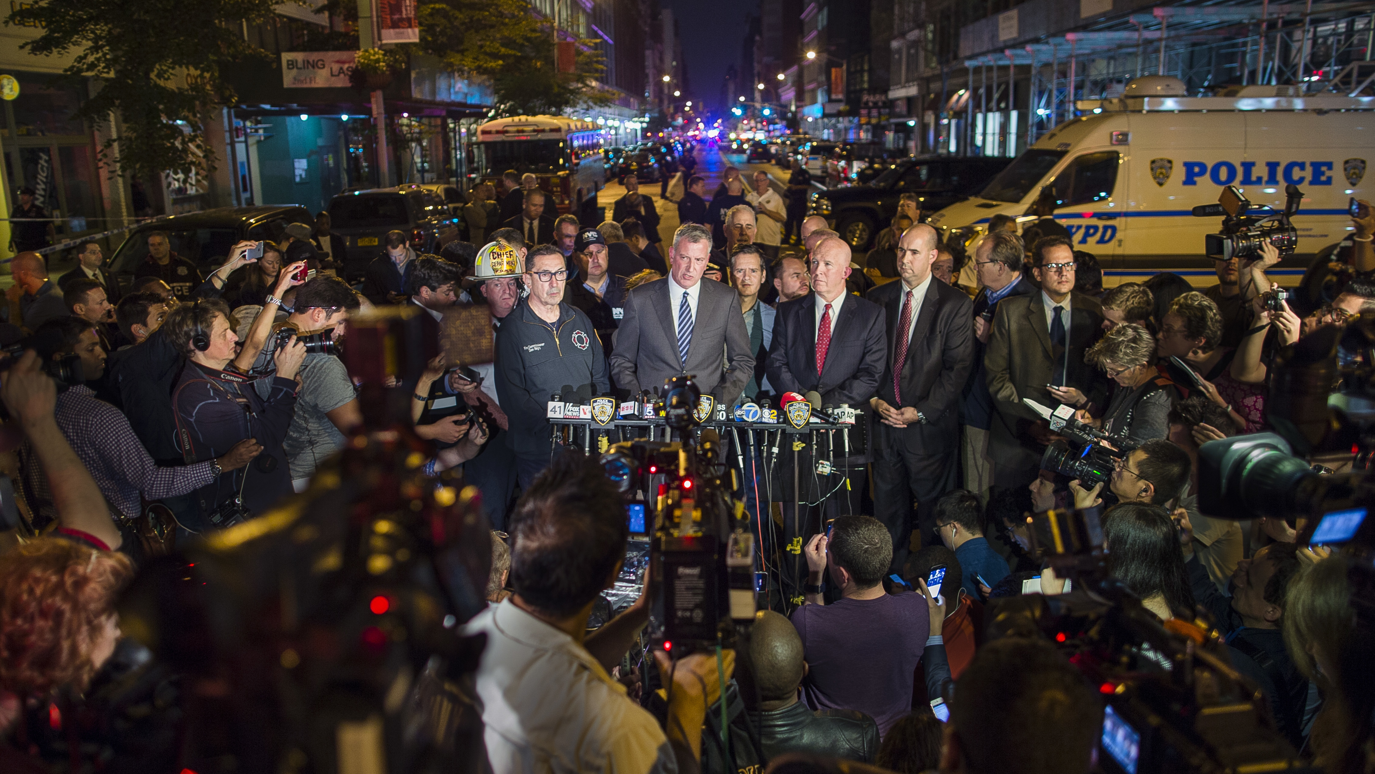 Mayor Bill de Blasio, center, and NYPD Chief of Department James O'Neill, center right, speak during a press conference near the scene of an apparent explosion on West 23rd street in Manhattan's Chelsea neighborhood, in New York, Saturday, Sept. 17, 2016. Police say more than two dozen people were injured in the explosion Saturday night.