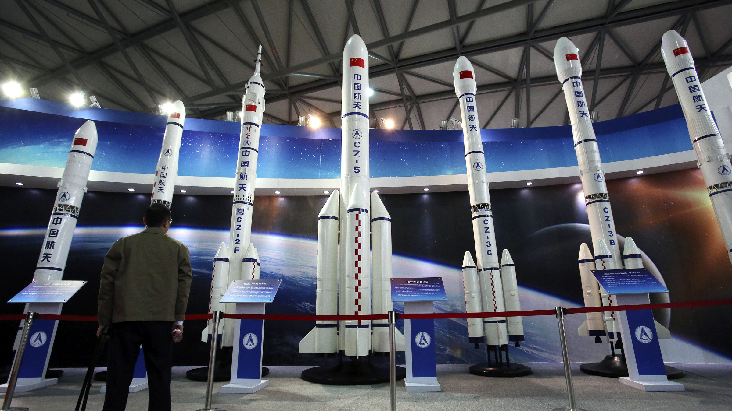 A visitor looks at the scale models of Chinese space rockets displayed at the China International Industry Fair in Shanghai, China, Tuesday, Nov. 5, 2013.