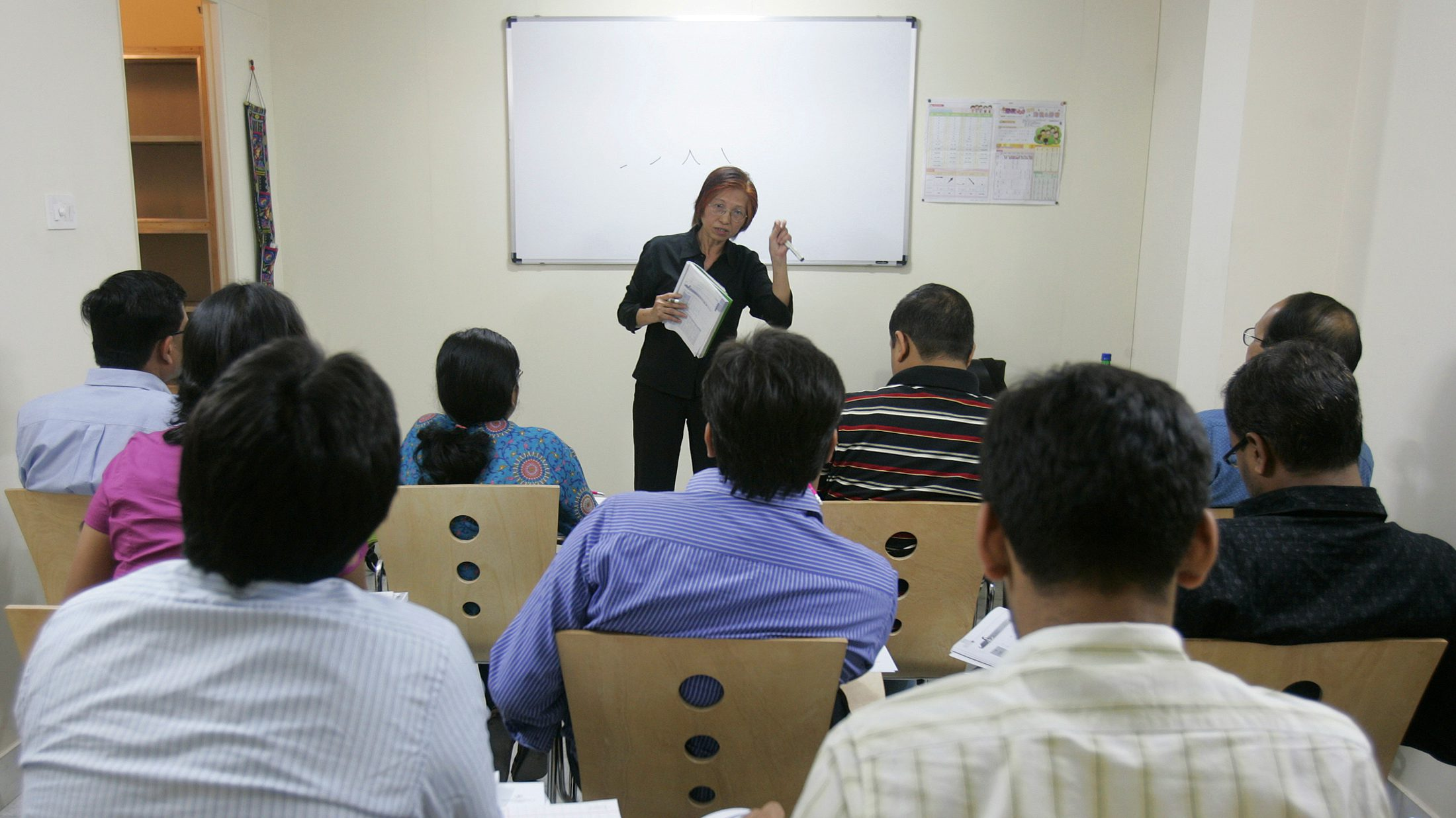 "A Chinese woman teaches the Chinese language to Indians at Zhong Wen Xue Xiao, the school of Chinese language in the eastern Indian city of Kolkata February 7, 2009. For the first time with the support of the Chinese consulate in Kolkata, a Chinese language school was set up last year followed by a monthly Chini Adda or Chinese Corner in January where both Chinese and non-Chinese people will gather to interact and promote cultural ties. Supported by the consulate, the Chini Adda is the brainchild of Madan Saraf, founder of the school of Chinese language. ""We hope to make the monthly gathering into a fortnightly affair."