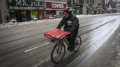 A pizza delivery man rides on a bicycle on 8th avenue in New York city.