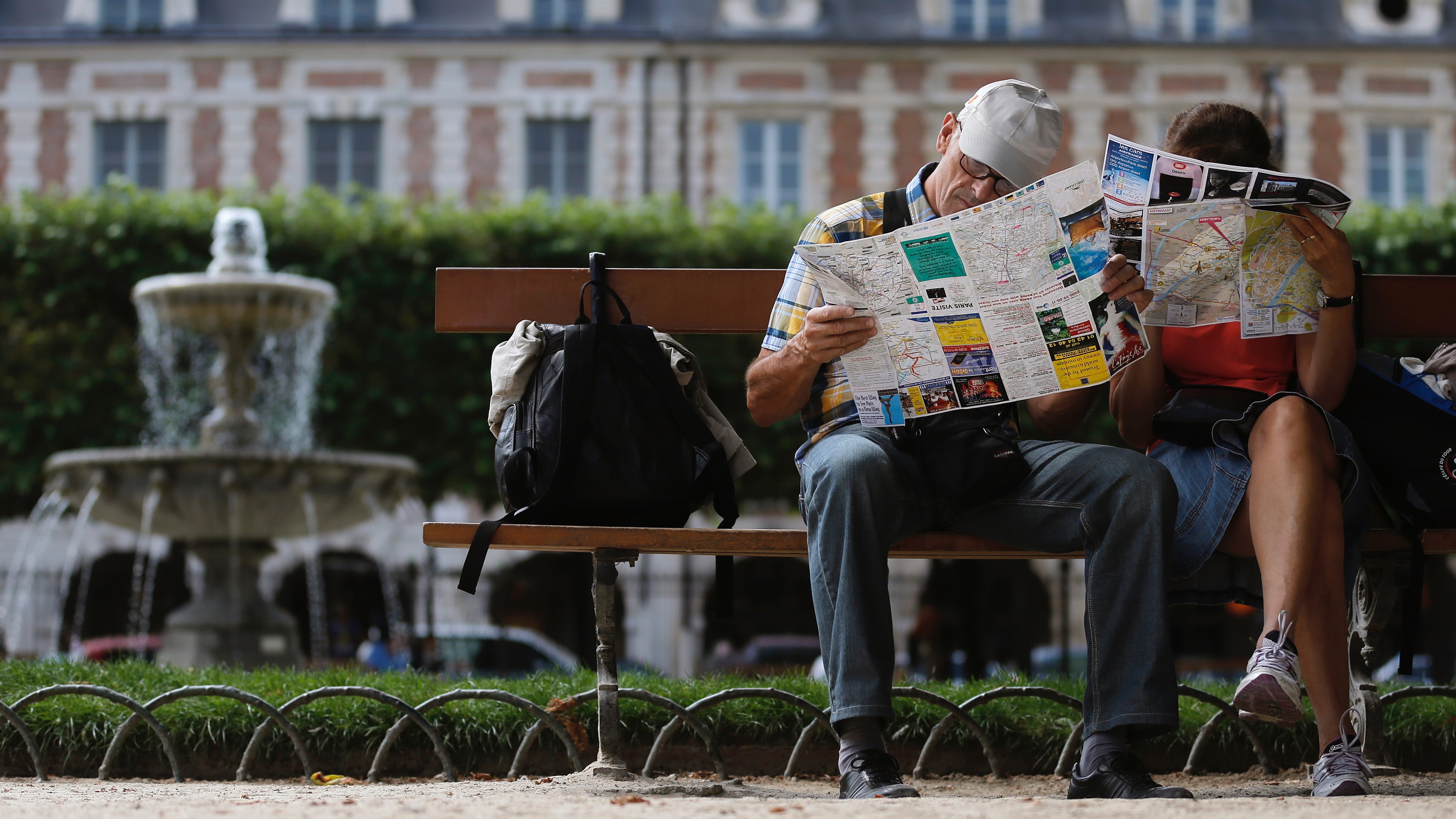 Tourists check city maps while sitting on a bench in the gardens at the Place des Vosges square, with landmark architecture of building that date from the seventeenth century, in Paris, August 14, 2013. REUTERS/Christian Hartmann (FRANCE - Tags: CITYSPACE SOCIETY TRAVEL) - RTX12KZF