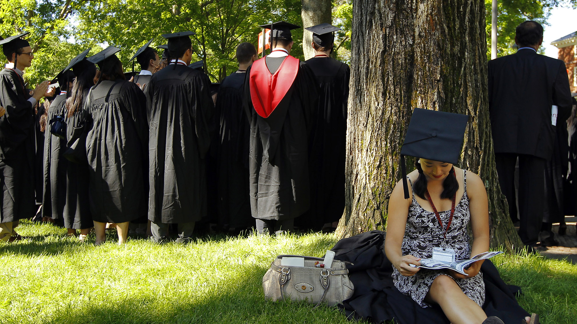 Graduating student Jennifer Lim sits in the shade before the start of the 361st Commencement Exercises at Harvard University in Cambridge, Massachusetts May 24, 2012.   REUTERS/Brian Snyder    (UNITED STATES - Tags: EDUCATION) - RTR32KVN