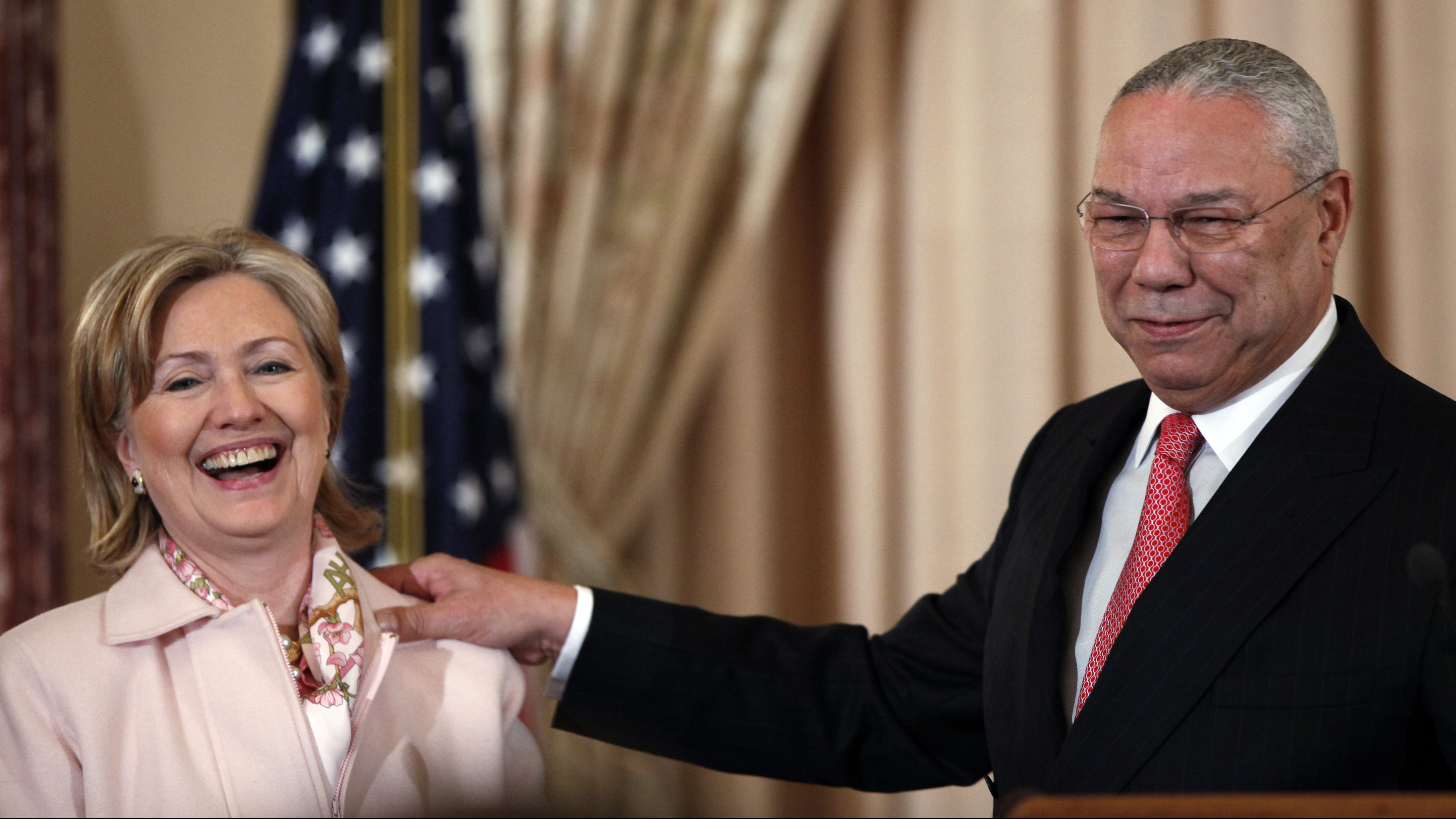 Former Secretary of State Colin Powell shares a laugh with then Secretary of State Hillary Rodham in 2009