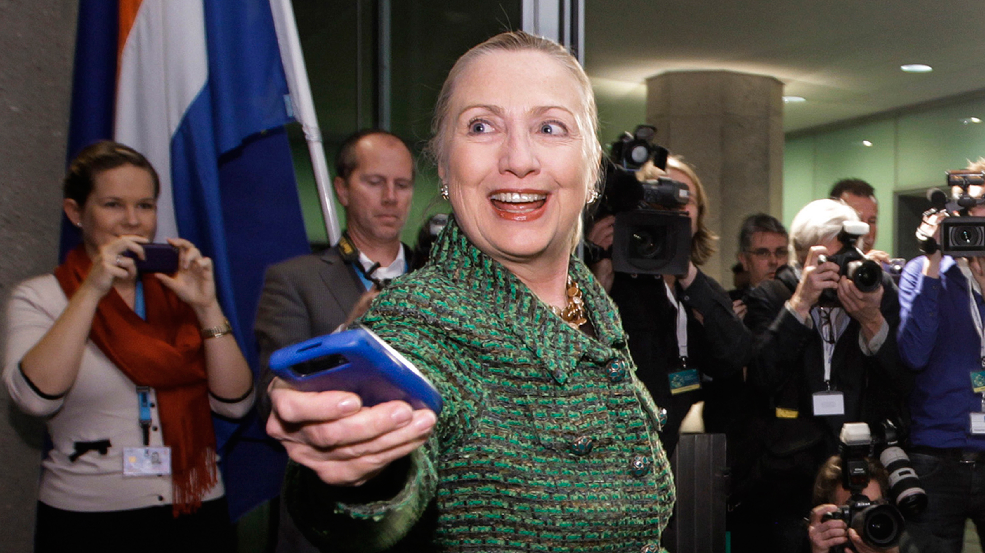 FILE - In this Dec. 8, 2011, file photo, then-U.S. Secretary of State Hillary Rodham Clinton hands off her mobile phone after arriving to meet with Dutch Foreign Minister Uri Rosenthal at the Ministry of Foreign Affairs in The Hague, Netherlands. Clinton emailed her staff on an iPad as well as a BlackBerry while secretary of state, despite her explanation that she exclusively used a personal email address on a homebrew server so she could carry a single device, according to documents obtained by The Associated Press. (AP Photo/J. Scott Applewhite, Pool/File)
