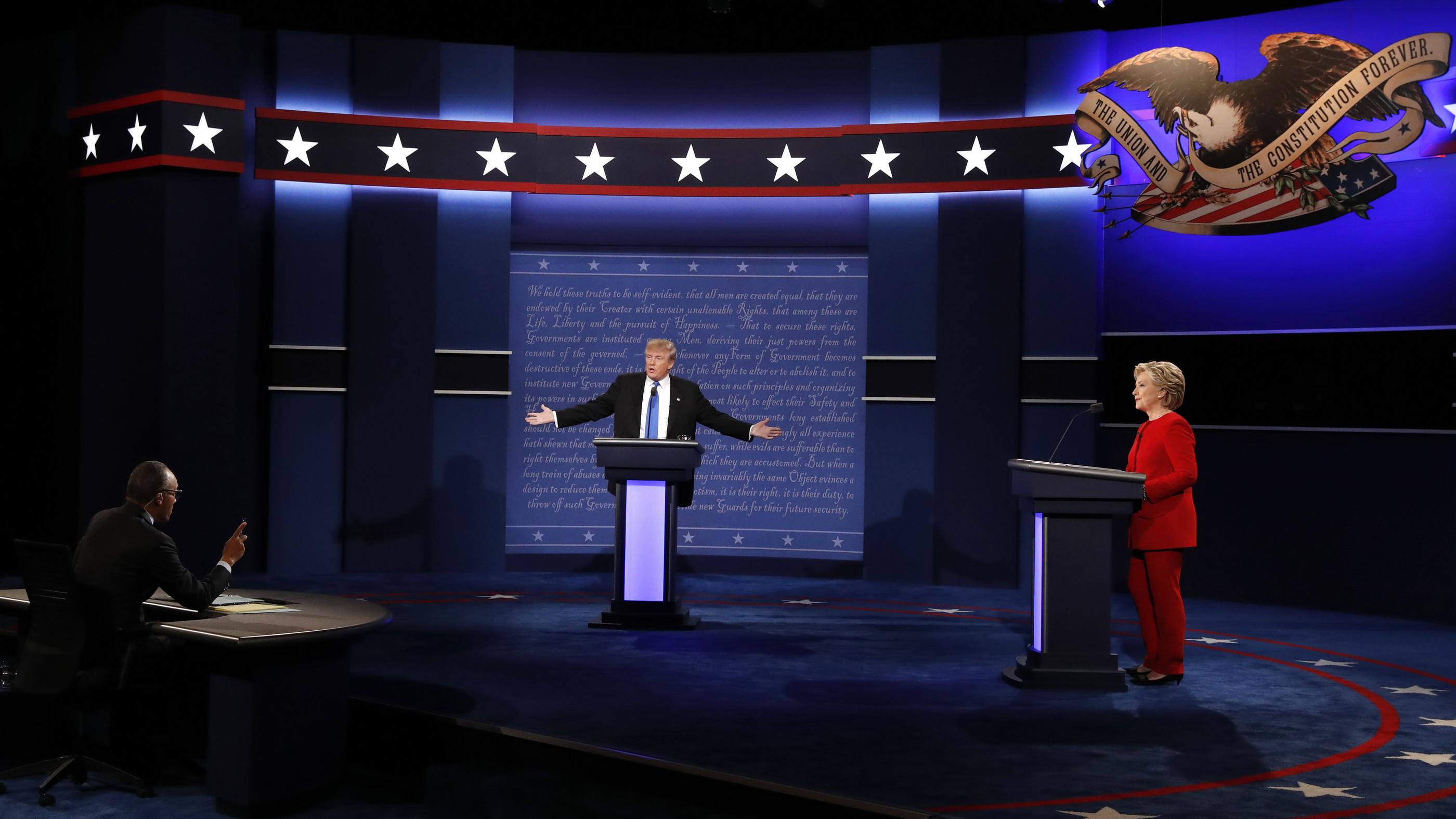 Republican U.S. presidential nominee Donald Trump speaks with debate host Lester Holt (L) as Democratic U.S. presidential nominee Hillary Clinton listens during their first presidential debate at Hofstra University in Hempstead, New York, U.S., September 26, 2016.