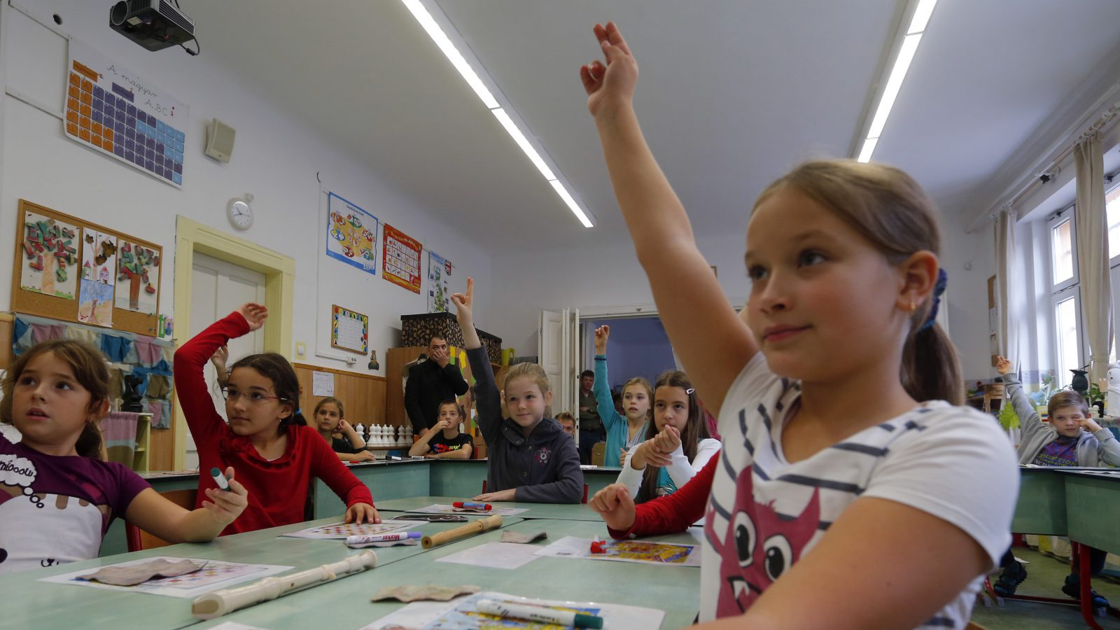 Children raise their hands during a presentation for visiting teachers at the Dezso Lemhenyi school, which uses the new Chess Palace teaching programme of the world's best female chess player Judit Polgar, in Budapest October 15, 2013. With names like Jumpy Horse, Boom Rook and Tiny Pawn, pieces in the Chess Palace come to life and are like close friends who guide the children through difficult school subjects. They range in size from 1 cm (under half an inch) tall to a meter (three feet) in height. Chairs, walls and carpets also sport chess motifs. The pieces, whose combinations and moves represent mathematical, linguistic or musical patterns, help children develop their skills in chess and in their school studies while making the learning process a more joyous exercise. Picture taken October 15, 2013. REUTERS/Laszlo Balogh (HUNGARY - Tags: SPORT CHESS EDUCATION SOCIETY) - RTX14MDC