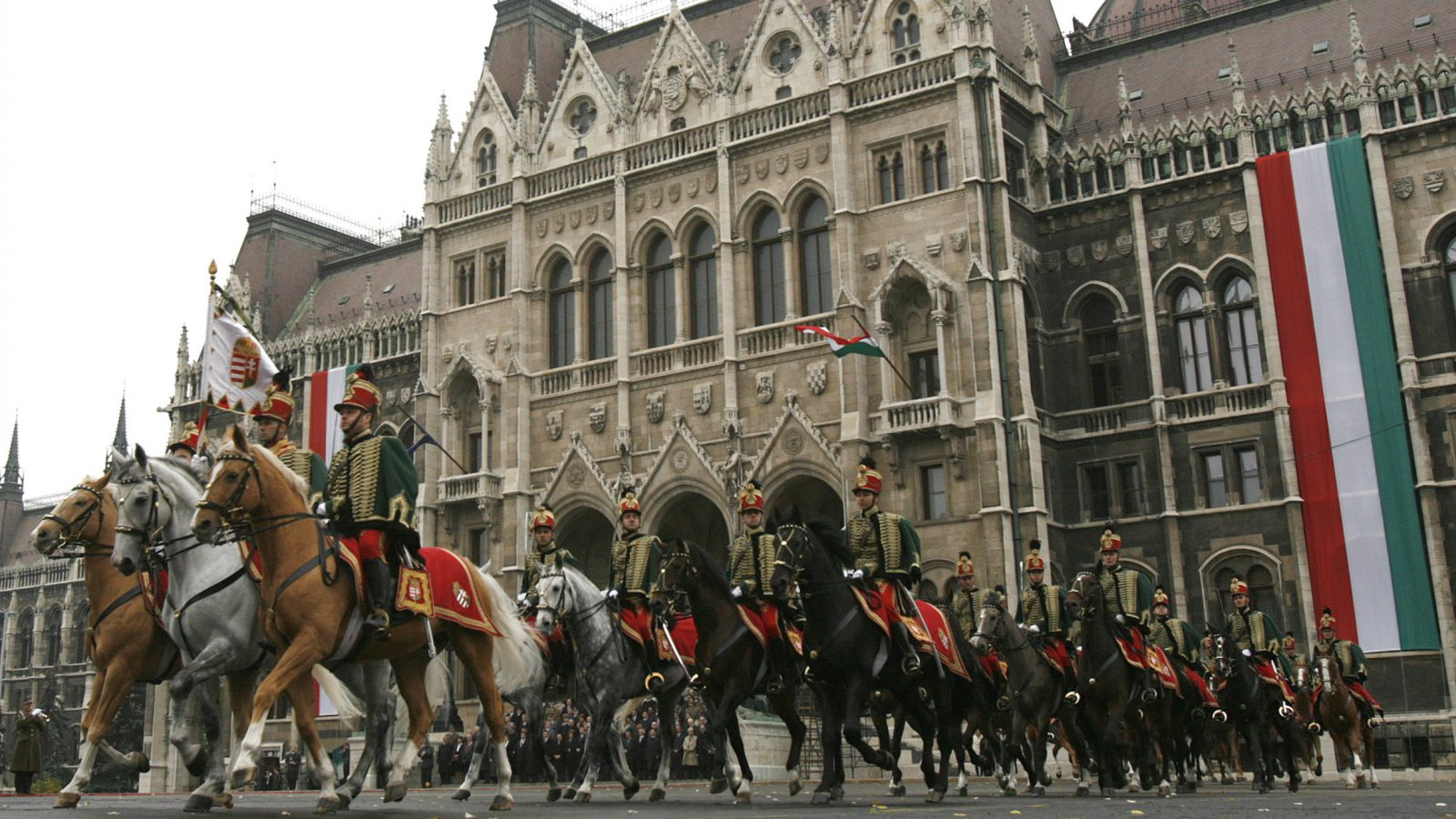 Hungarian Hussars ride their horses in front of the parliament building in Budapest October 23, 2008 during a commemoration of Hungary's 1956 anti-communist revolution.