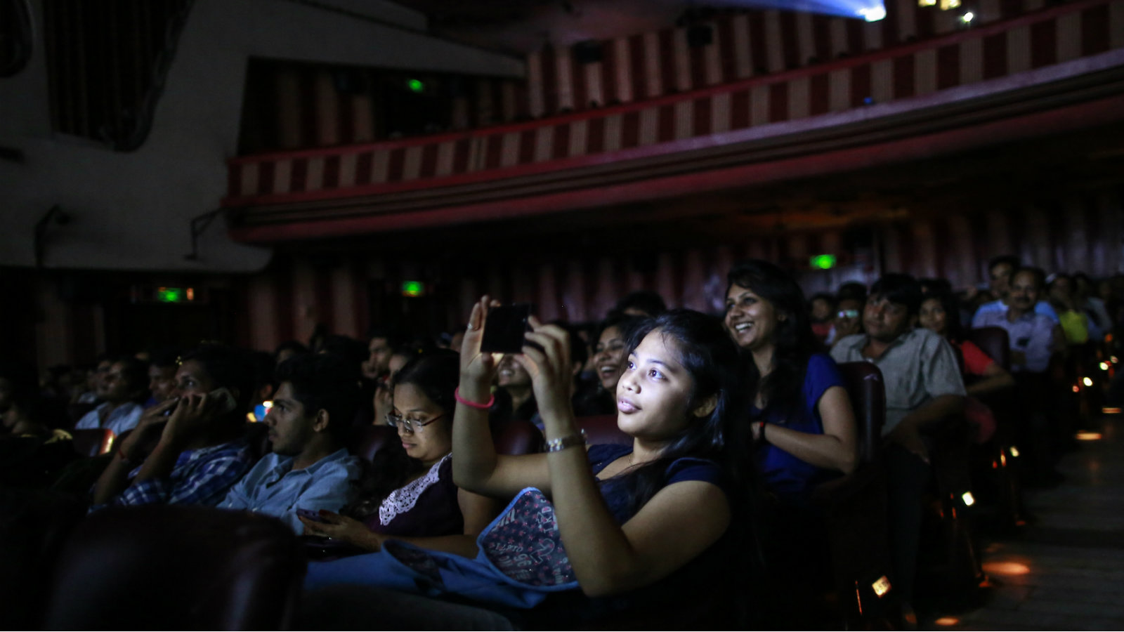 """A cinema goer takes a picture as others watch Bollywood movie """"Dilwale Dulhania Le Jayenge"""" (The Big Hearted Will Take the Bride), starring actor Shah Rukh Khan, inside Maratha Mandir theatre in Mumbai December 12, 2014. The movie, released in October 1995, has set a record of completing 1000 weeks of continuous screening at a cinema, a feat unmatched by any other Bollywood movies. According to Manoj Desai, owner of the theatre, the movie, which is still being screened, enjoys at least 50 to 60 percent occupancy on weekdays and full house on weekends at his theatre. The movie is screened only in the morning and the ticket price ranges from 15 to 20 Indian rupees ($0.24-$0.32)."""