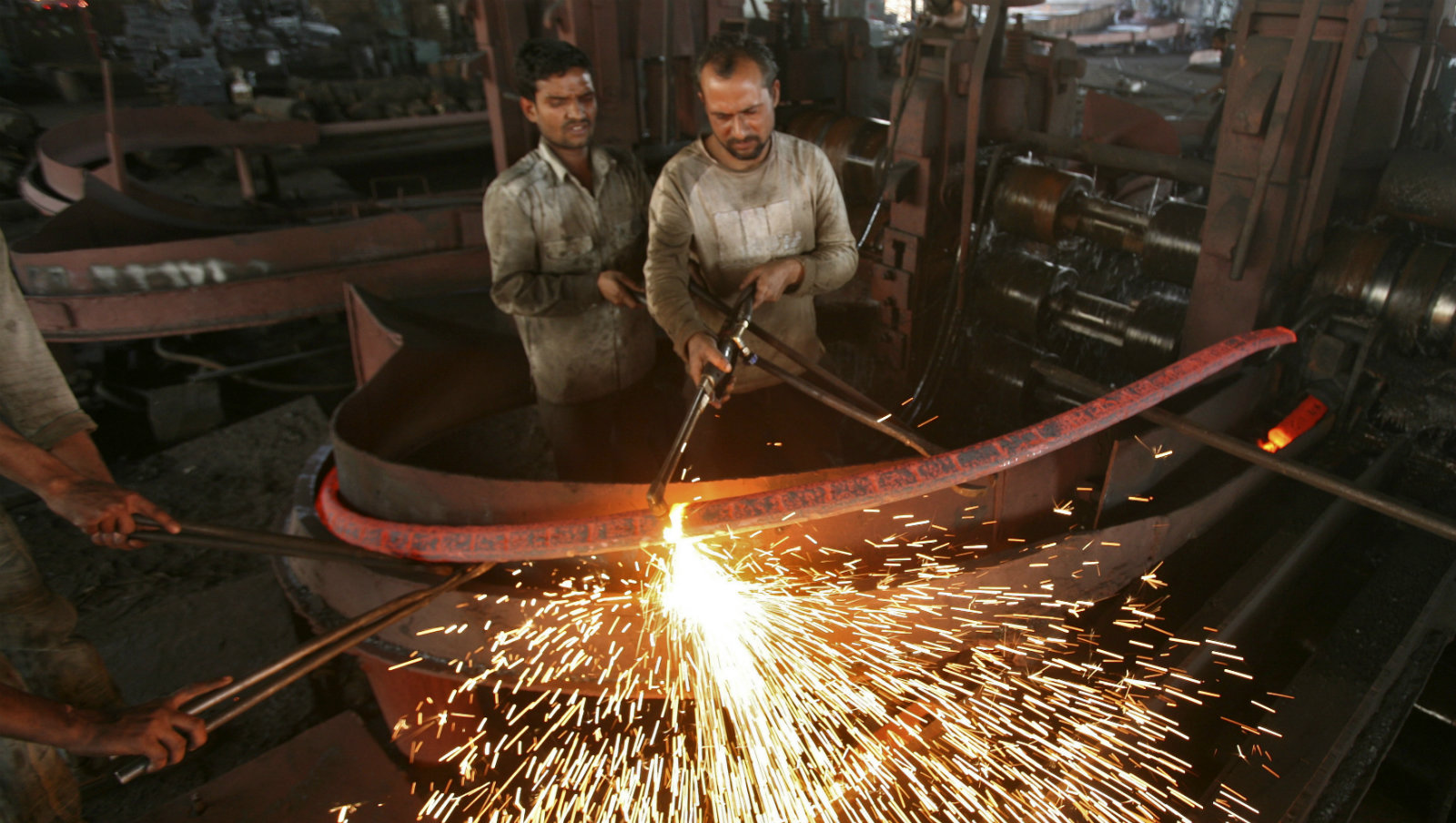 Labourers work inside an iron factory on the outskirts of Jammu November 12, 2012. India's economic gloom deepened on Monday with a surprise contraction in industrial production, a fall in exports and higher retail inflation, dashing hopes of a quick revival in an economy on track to post its slowest growth in a decade.