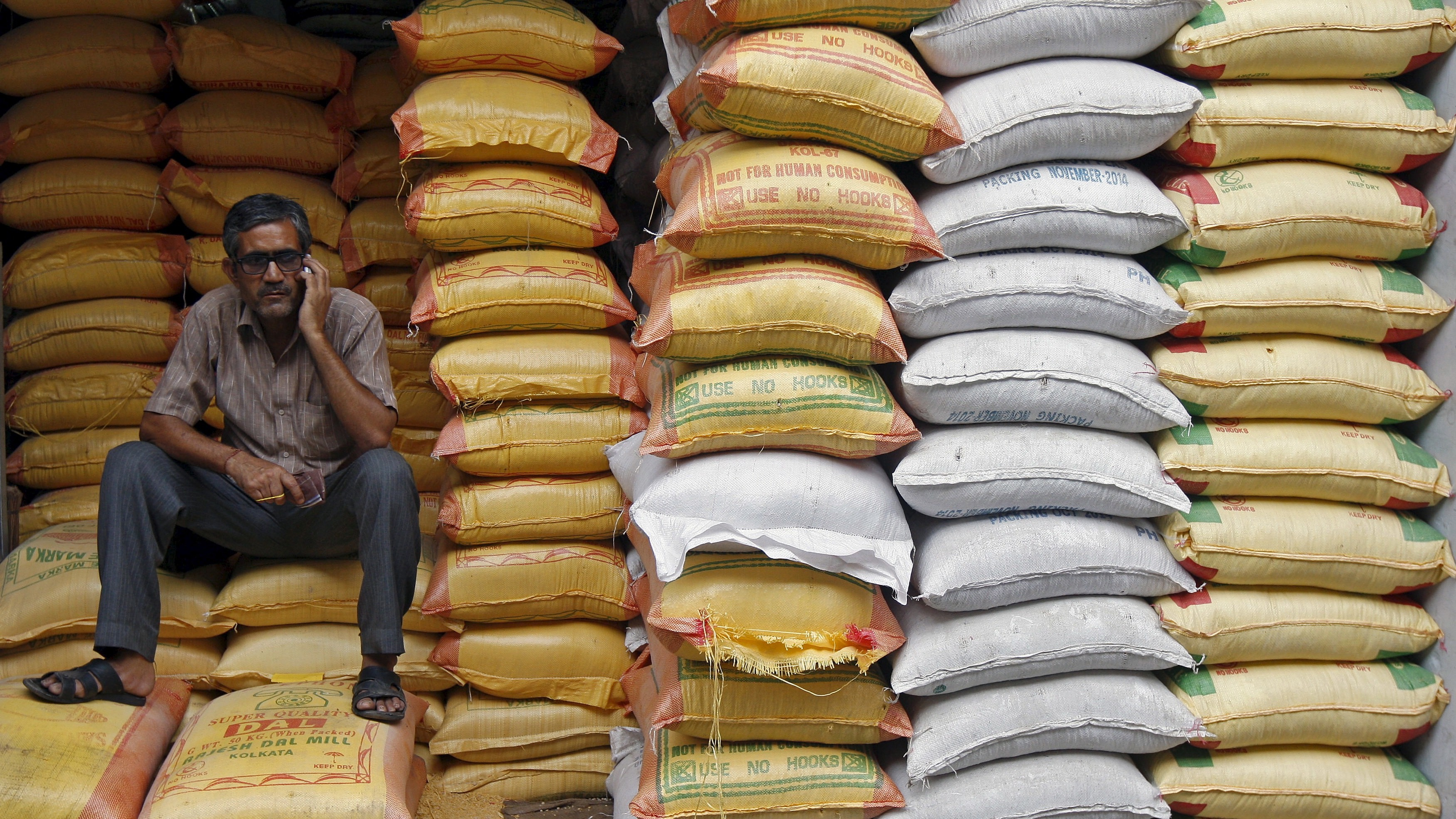 A worker speaks on a mobile phone as he sits inside a shop selling cereal, grains, and pet food, in Kolkata April 15, 2015. India's annual wholesale prices declined at their fastest pace in at least nine years in March on cooling oil and manufacturing costs, reflecting trends that could give the central bank room to make further interest rate cuts. REUTERS/Rupak De Chowdhuri - RTR4XFXC