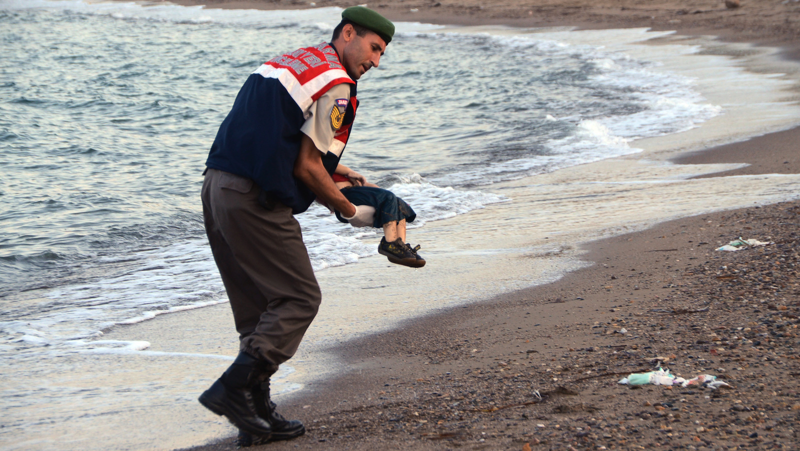 A paramilitary police officer carries the lifeless body of Syrian refugee Alan Kurdi.