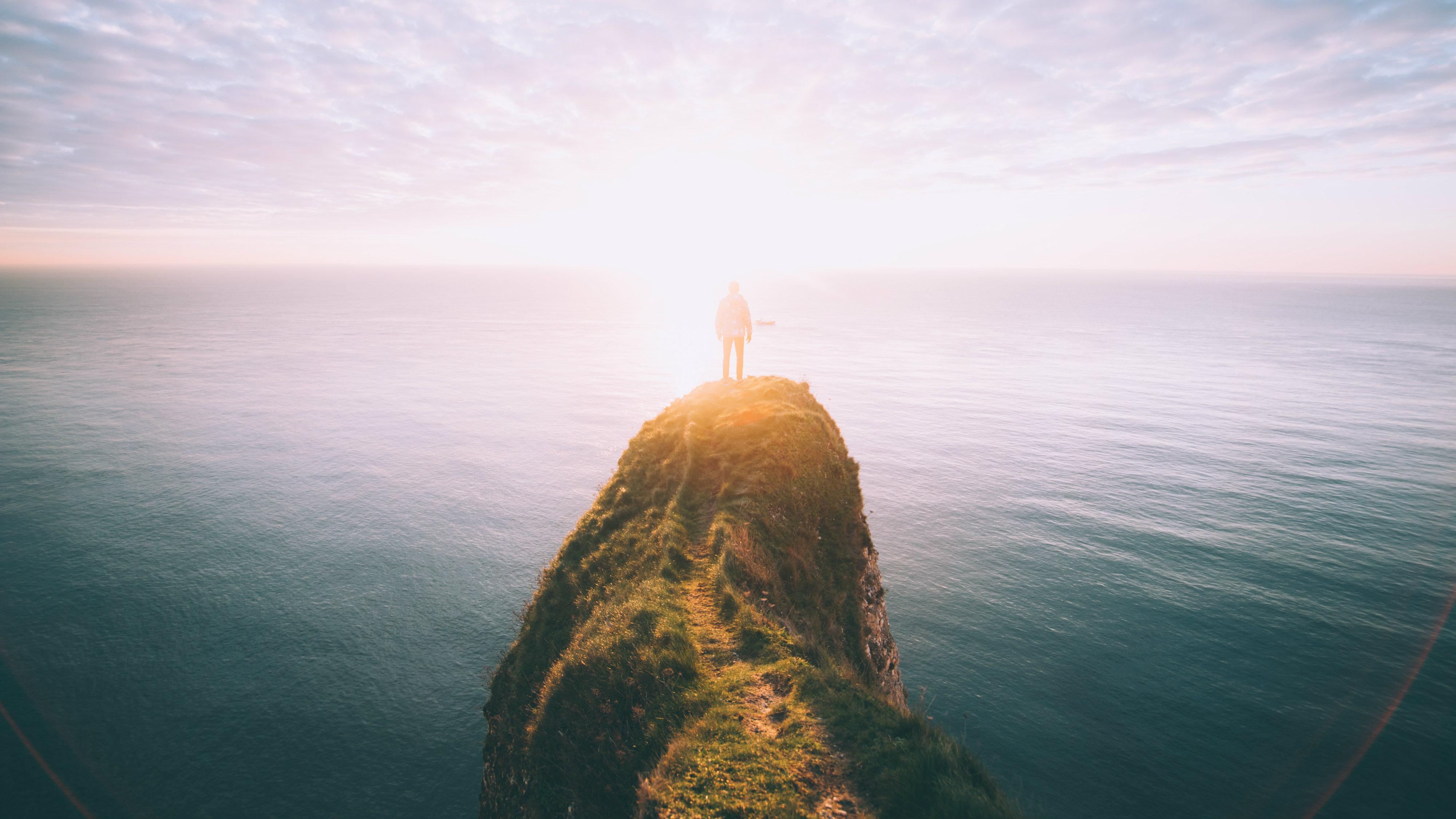 Man looking at ocean from precipice