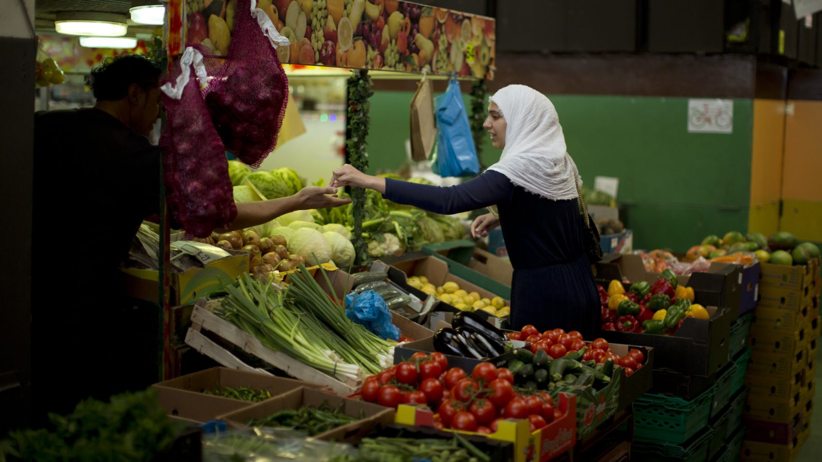 In this Tuesday, July 5, 2016 photo, a woman buys vegetables at a market in downtown Peterborough, East of England. An hour by train from London, Peterborough has experienced a rapid demographic shift, with the arrival of more than 30,000 migrants since the turn of the century. (AP Photo/Emilio Morenatti)