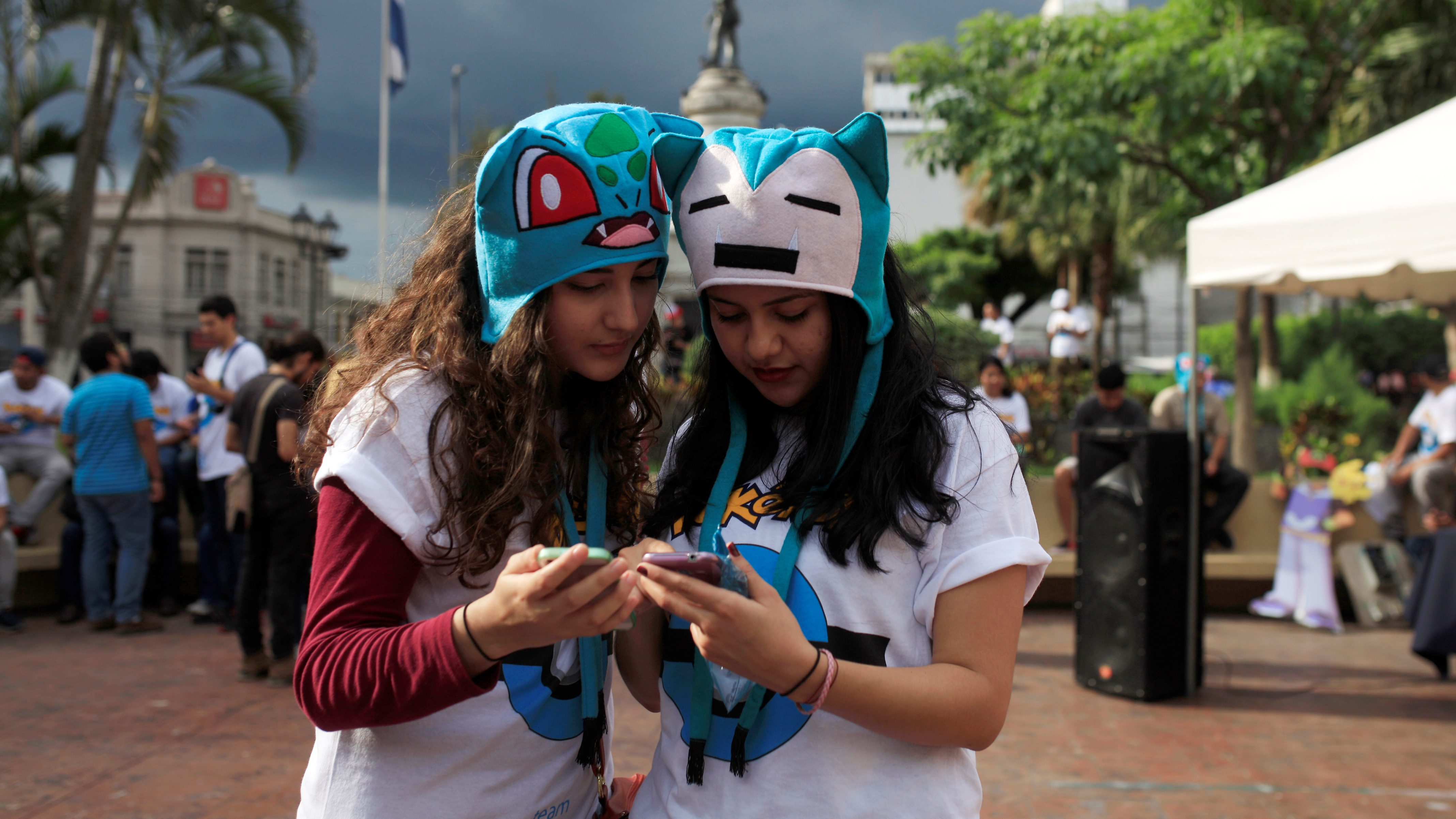 "People play the augmented reality mobile game ""Pokemon Go"" by Nintendo on their mobile phone during a pokeour organized by the municipality in San Salvador"