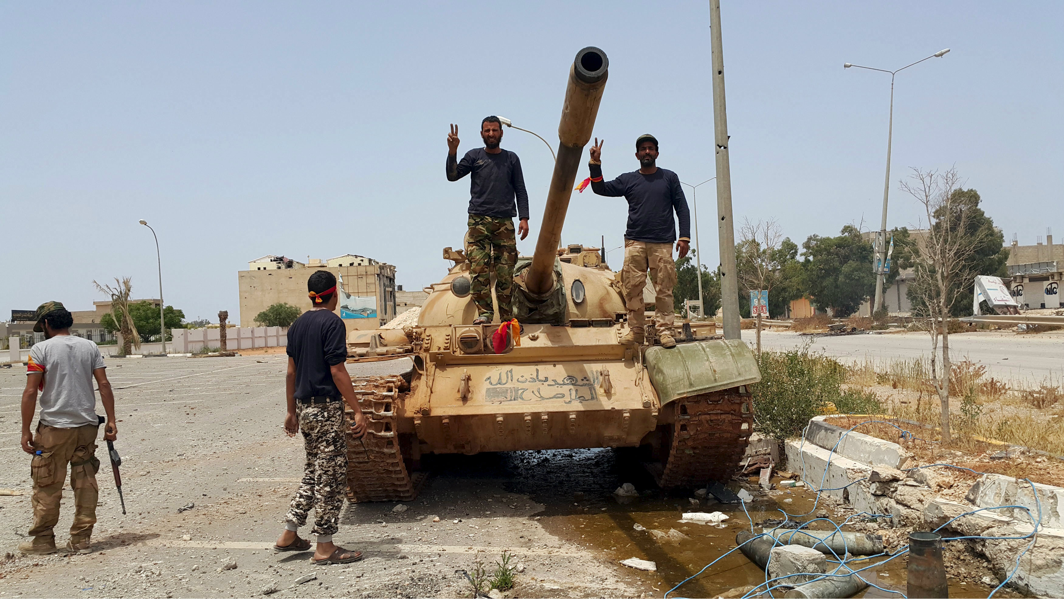 Members of the Libyan pro-government forces gesture as they stand on a tank in Benghazi, Libya, May 21, 2015.