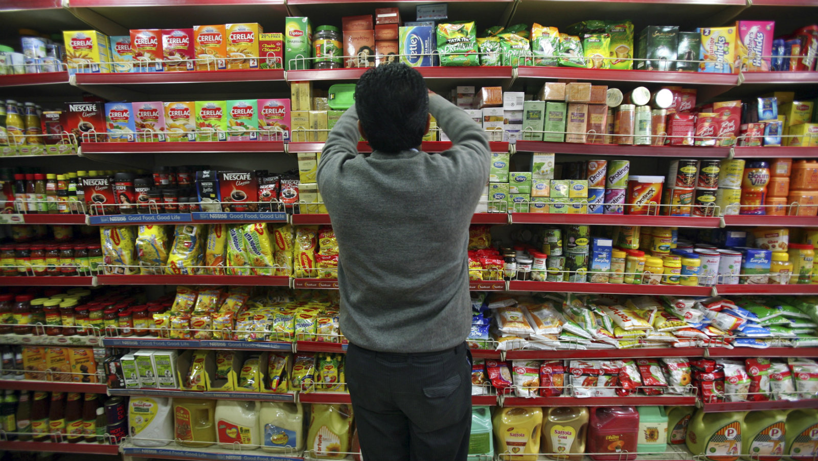 A worker arranges the shop shelf at a grocery store in Jammu.