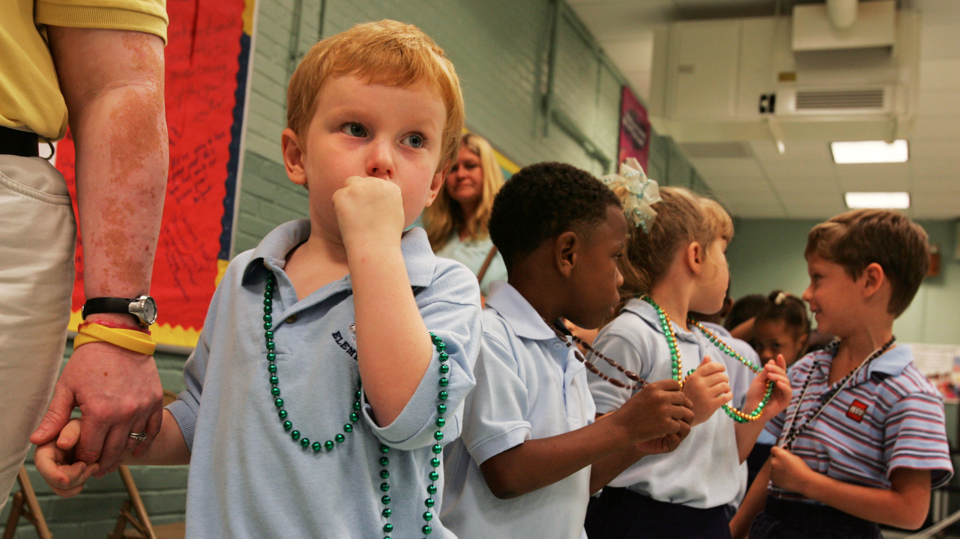 Pre-schooler Cecil Smith (L), 4, holds the hand of a teacher's assistant as he prepares to go to class after he and classmates were given Mardi Gras beads, on the first day of school since Hurricane Katrina hit over a month ago, at an elementary school in Metairie, Louisiana October 3, 2005.