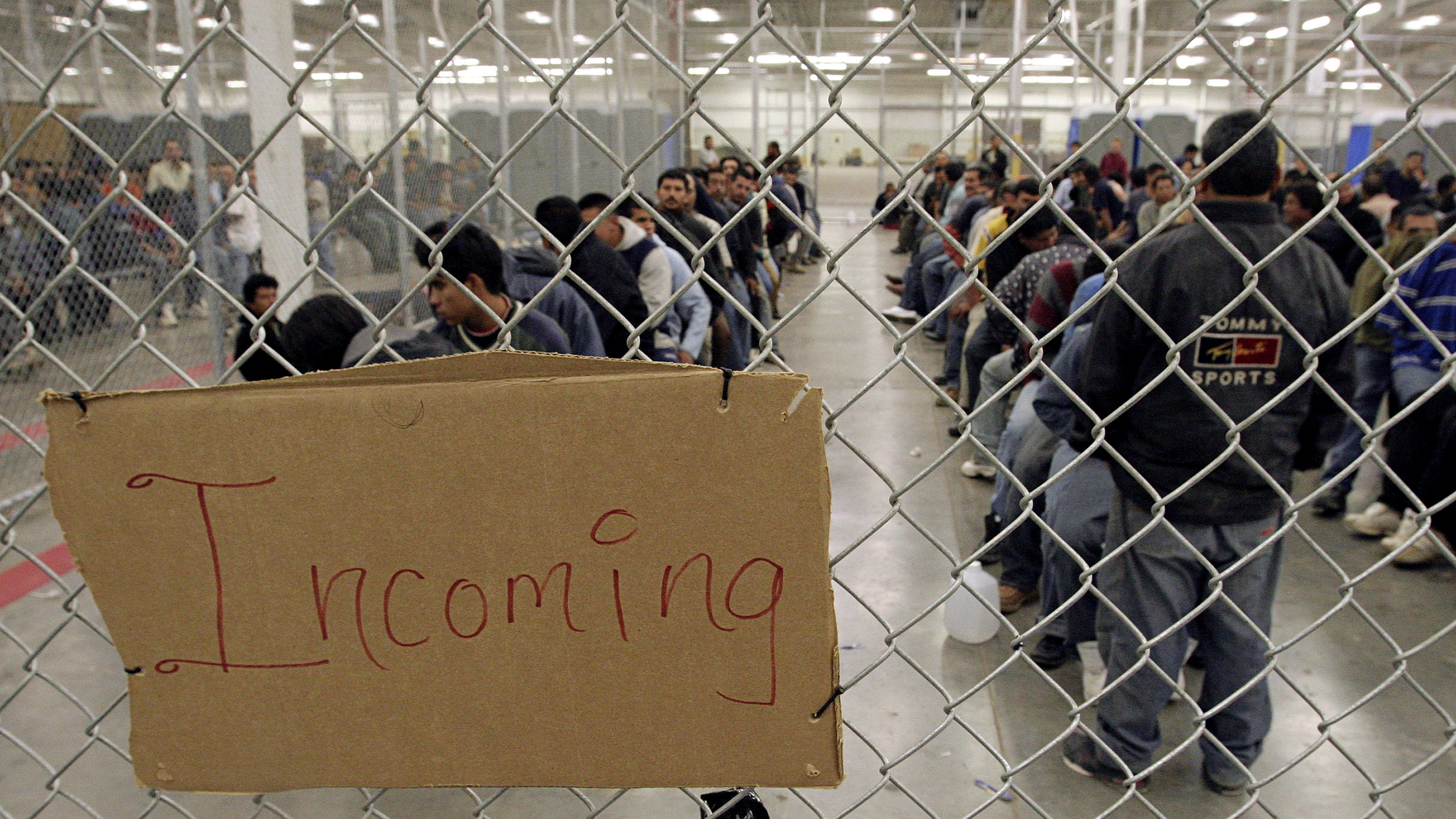 Undocumented immigrants wait in a holding facility after arriving at the U.S. Border Patrol detention center in Nogales, Arizona, May 31, 2006. REUTERS/Jeff Topping - RTR1DYVB