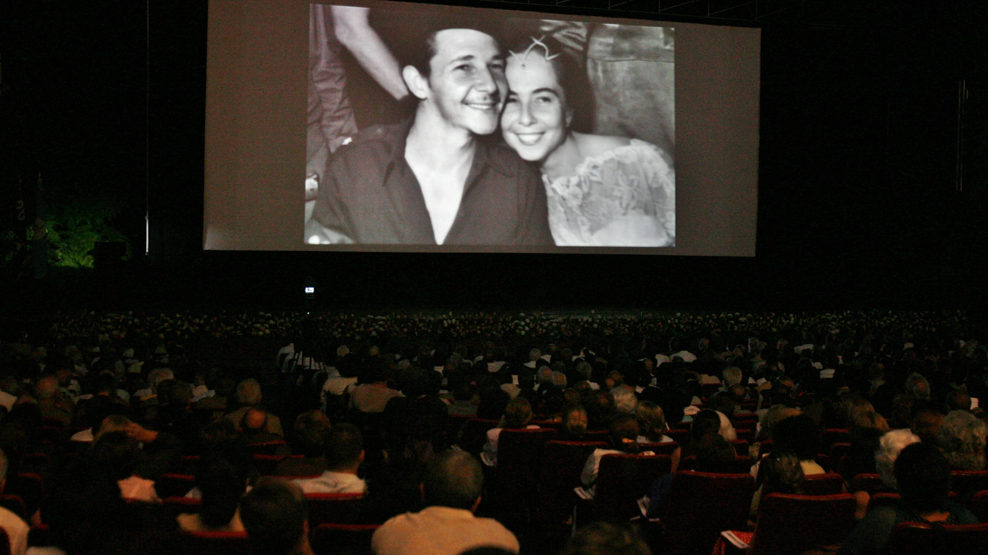 The audience looks at photographs of Cuba's acting President Raul Castro and Vilma Espin on their wedding day during the screening of a documentary on the life of Espin at the Karl Marx Theater in Havana June 19, 2007. Espin, sister-in-law of convalescing Cuban leader Fidel Castro and one of the most powerful women in Cuba's political leadership, died on Monday in Havana. She was 77. REUTERS/Claudia Daut (CUBA) - RTR1QYJ2