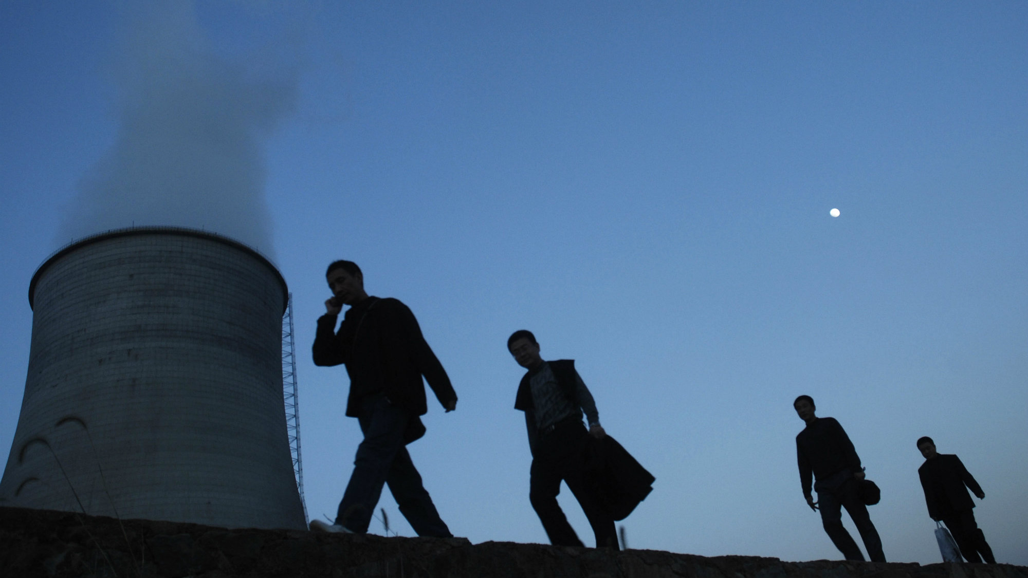 People walk on a street past a power plant's cooling tower in China.