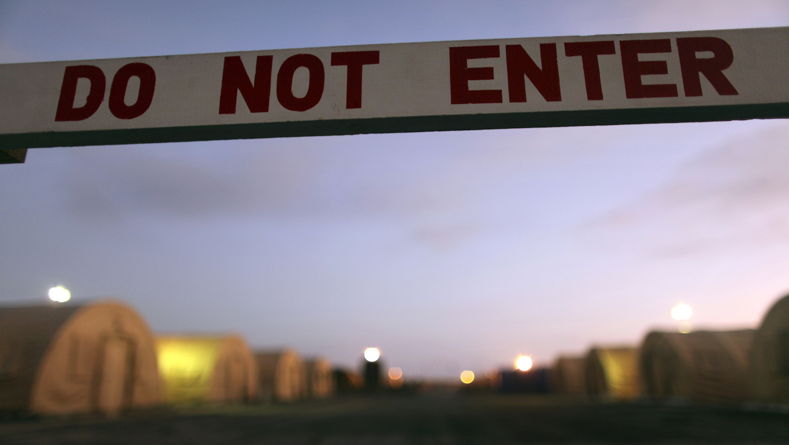 In this photo, reviewed by the U.S. Military, a sign marks a closed-off area, at Camp Justice, the location of the U.S. Military Commissions court for war crimes, at the U.S. Naval Base, in Guantanamo Bay, Cuba, January 19, 2009. Military judges in Guantanamo pressed forward Monday with hearings for five men accused of orchestrating the Sept. 11 attacks and for a Canadian accused of killing a U.S. soldier.    REUTERS/Brennan Linsley/Pool    (CUBA) - RTR23LPB