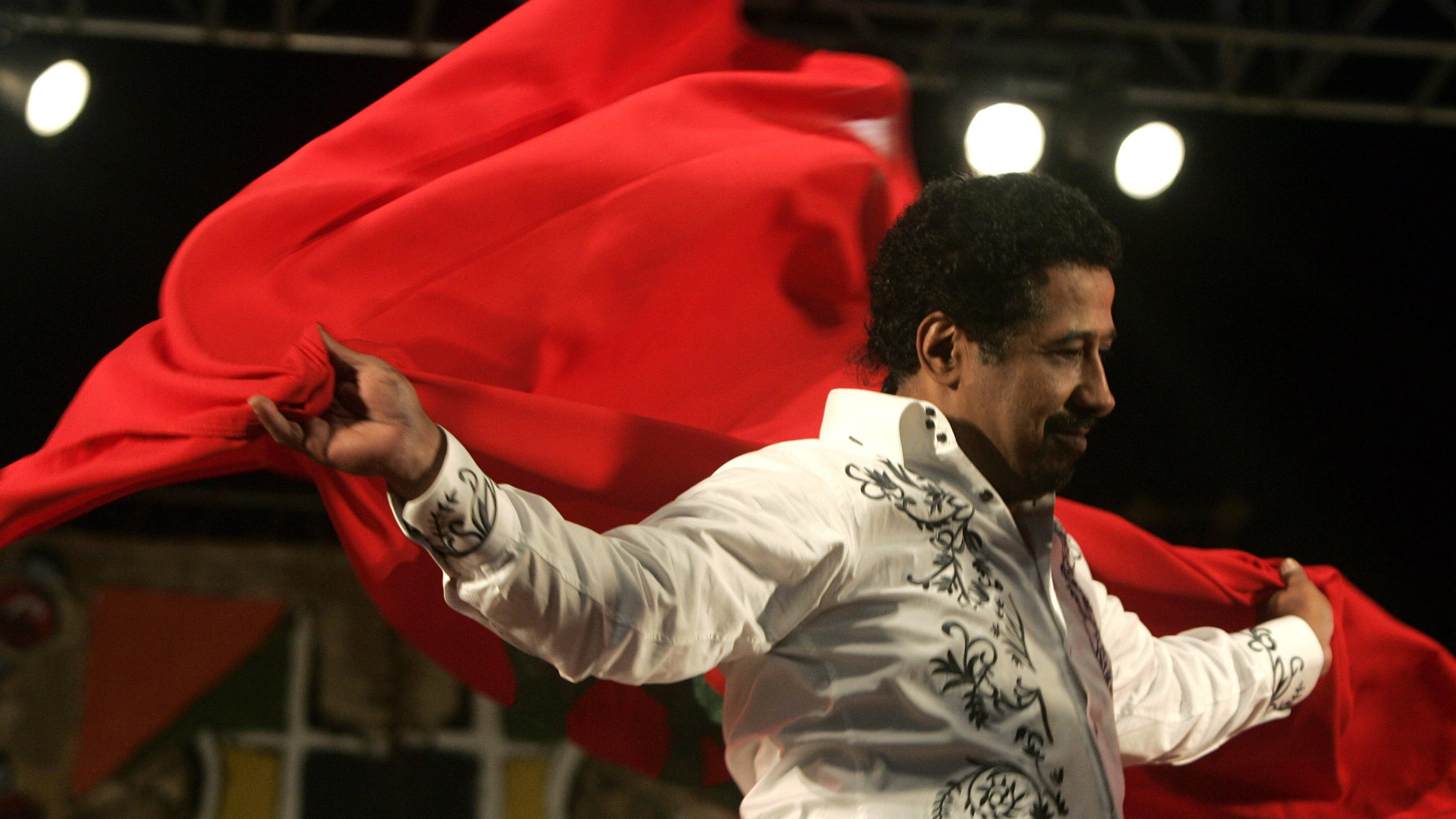 Algerian singer Cheb Khaled (Khalid) covers himself with a Moroccan flag during his concert in Essaouira