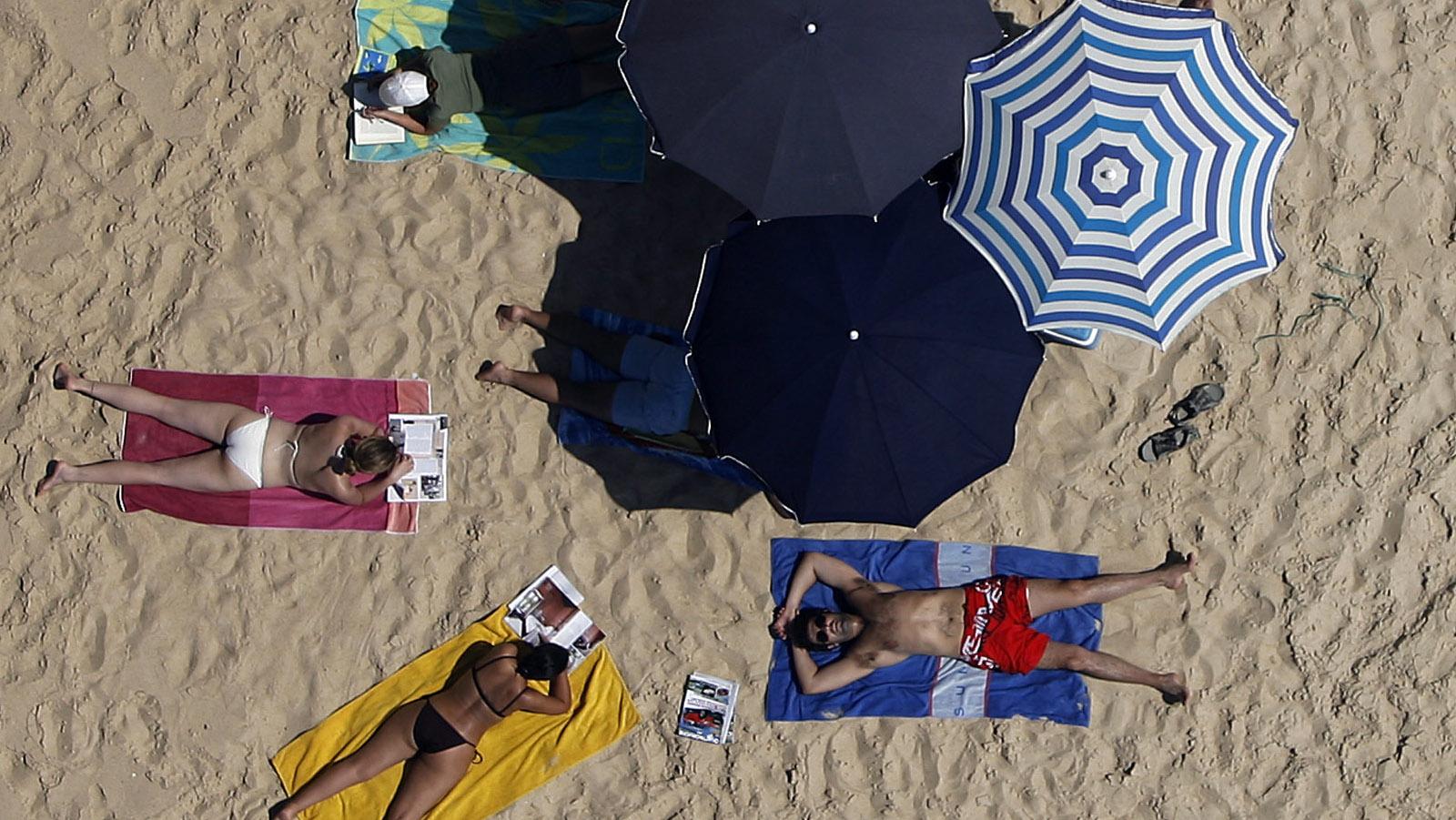 People sunbathe on a beach of Pinheiro da Cruz