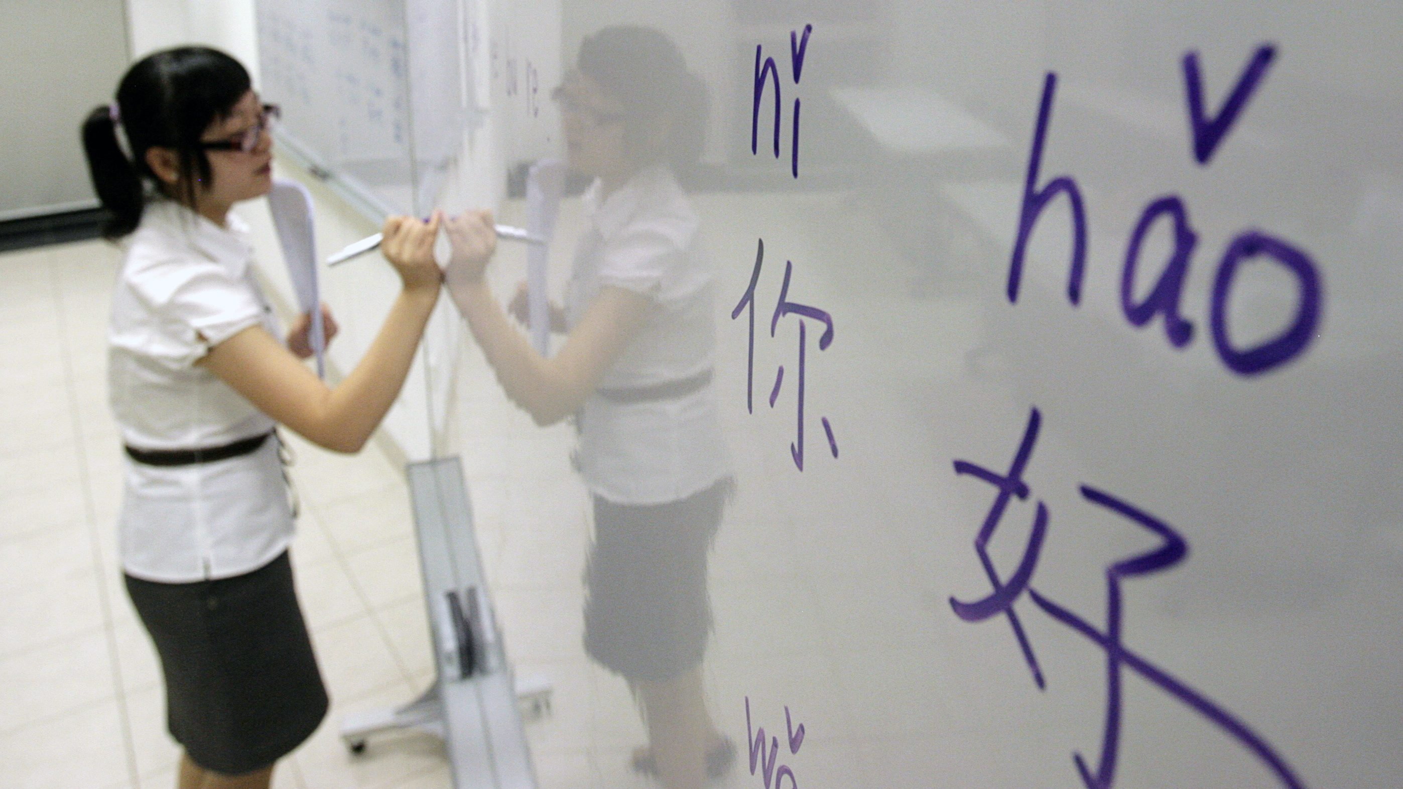 An instructor writes mandarin characters on a whiteboard at a night class for people learning mandarin as a second language in Singapore September 1, 2009. English has long united the ethnically diverse island-state but Singapore's leaders now foresee a time when Mandarin will be the country's dominant language and they are aggressively encouraging their people to become fluent in Chinese. To match feature