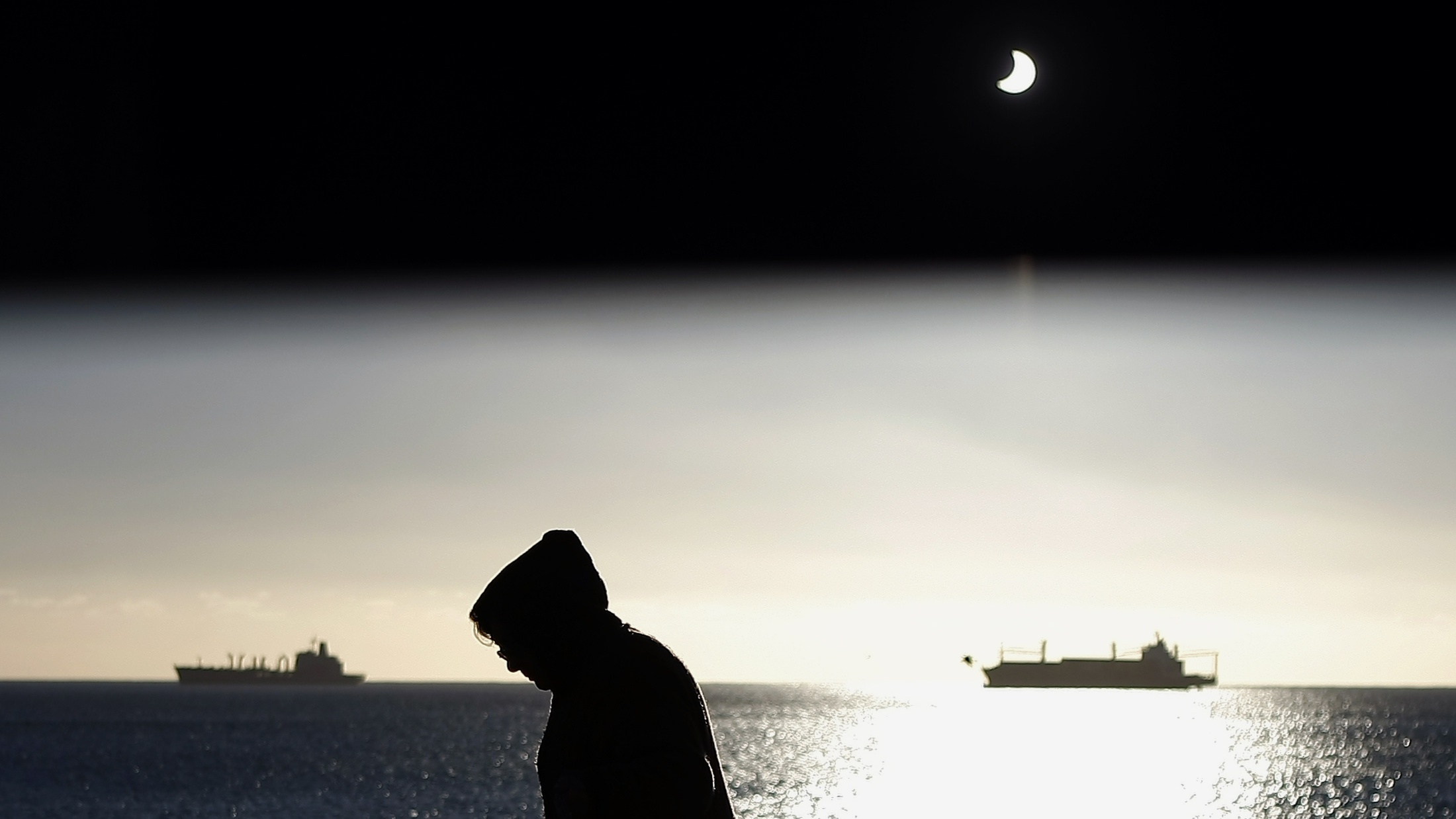 The moon passes between the sun and the earth during a solar eclipse in Valparaiso City, 75 miles (121 km) northwest of Santiago, July 11, 2010. The effect was created by shooting part of the image through a piece of exposed X-ray film. REUTERS/Eliseo Fernandez (CHILE - Tags: SCI TECH ENVIRONMENT IMAGES OF THE DAY)