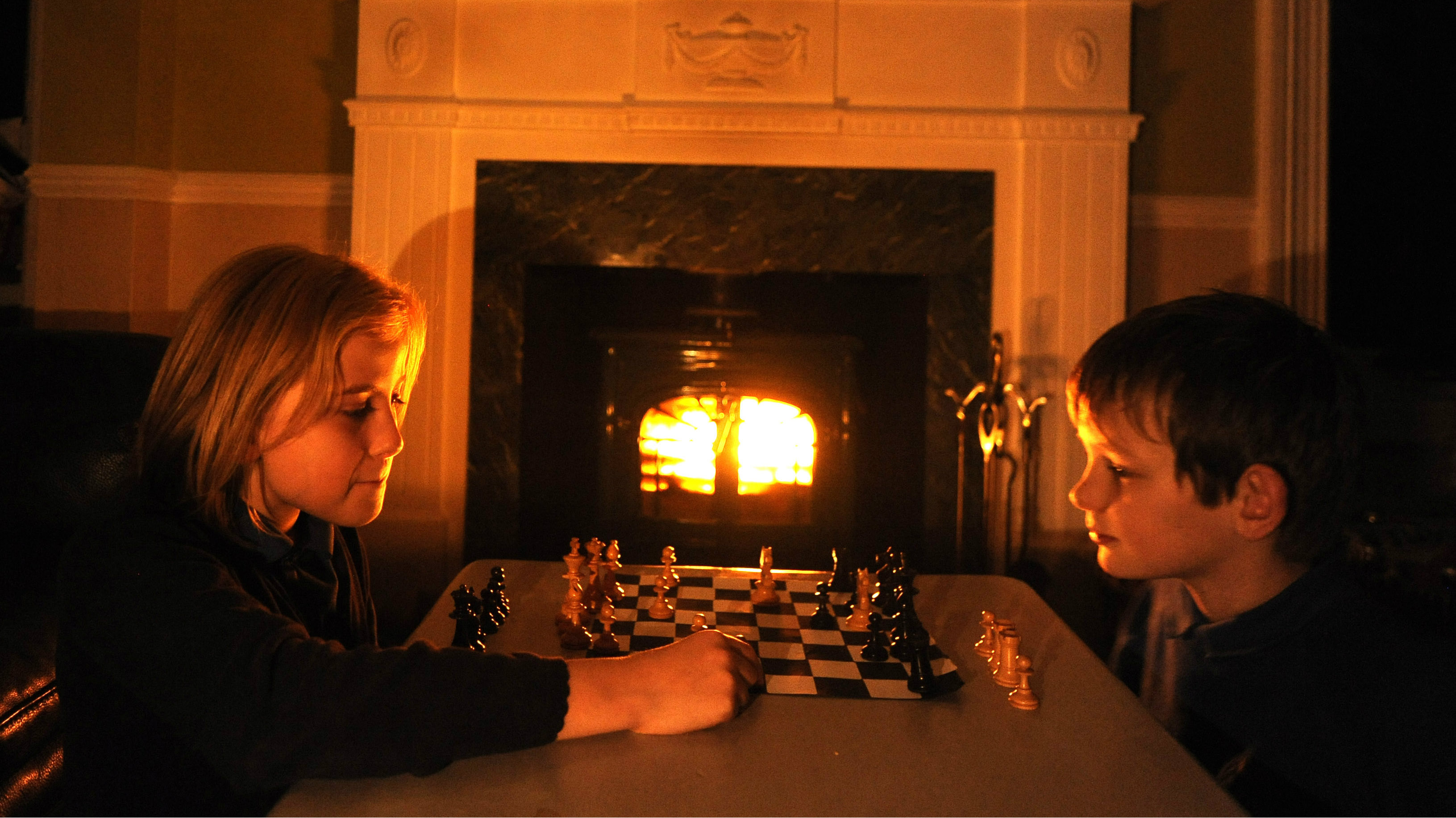 Elsie and Euan play chess by candle light following a power cut in Pitlochry,Scotland