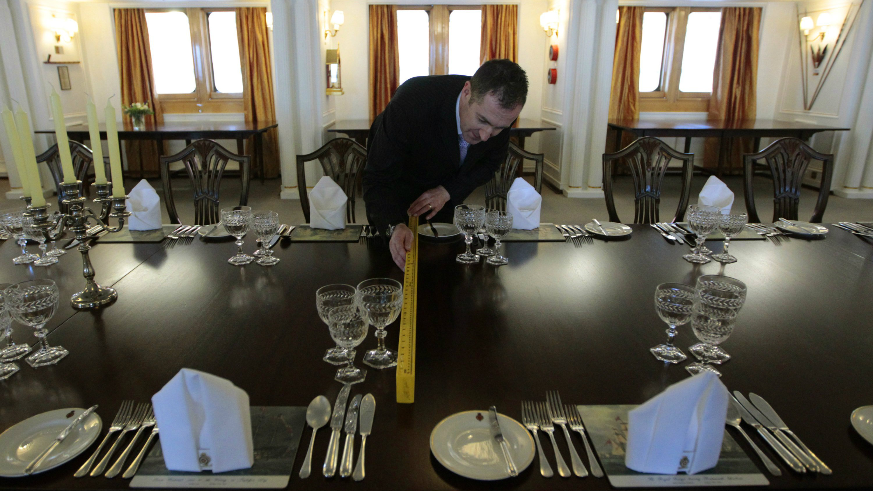 Fine dining manager Bruce MacBride checks the table settings in the dining room of the Royal Yacht Britannia in Edinburgh, Scotland January 31, 2012.