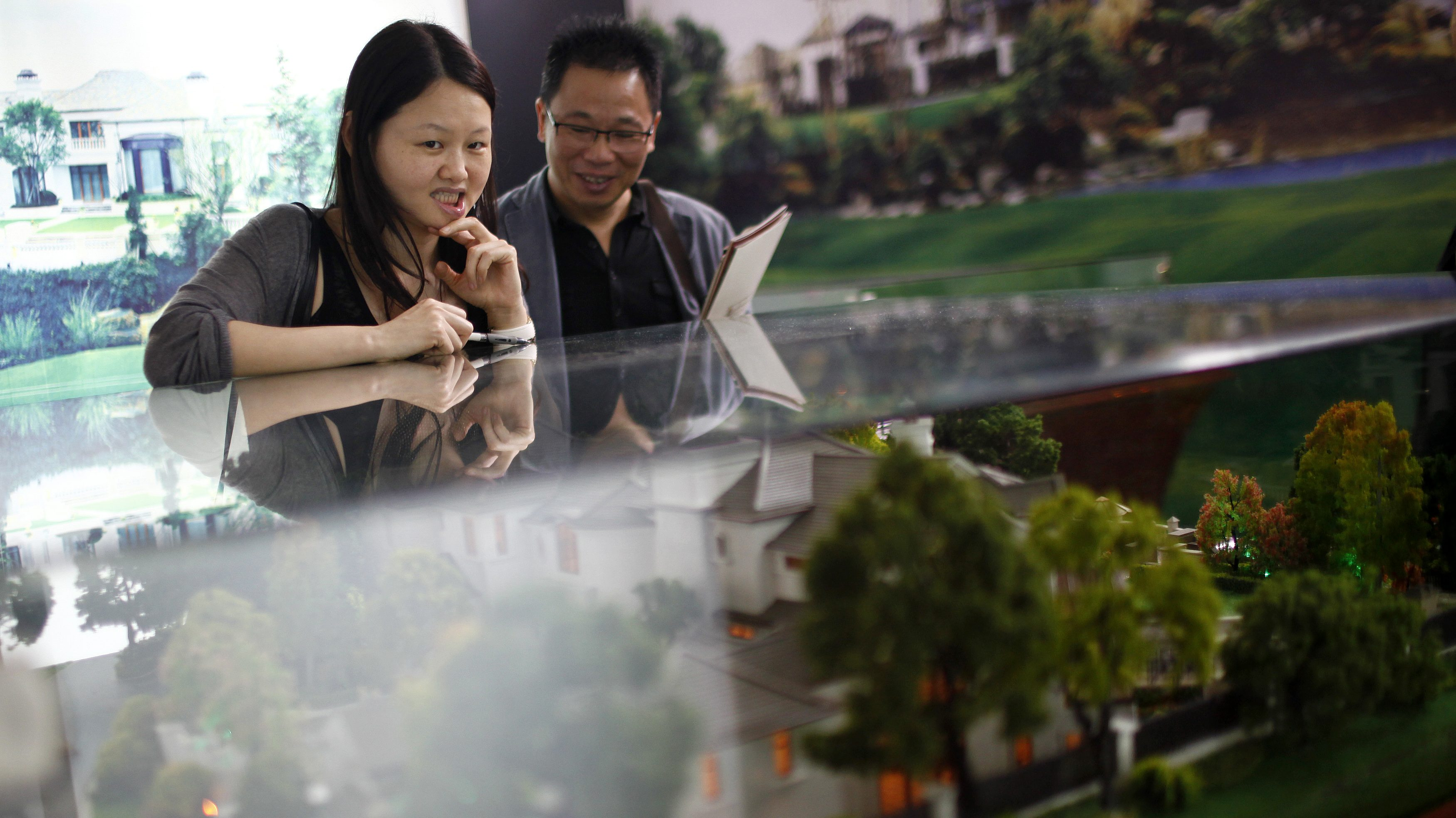 A couple visit a real estate stand during the 2012 Spring Real Estate exhibition in Shanghai May 1, 2012. China may introduce preferential policies for first-home buyers to help support the property market, the Shanghai Securities News reported on Tuesday, citing unidentified sources.  REUTERS/Carlos Barria  (CHINA - Tags: BUSINESS REAL ESTATE) - RTR31FUD