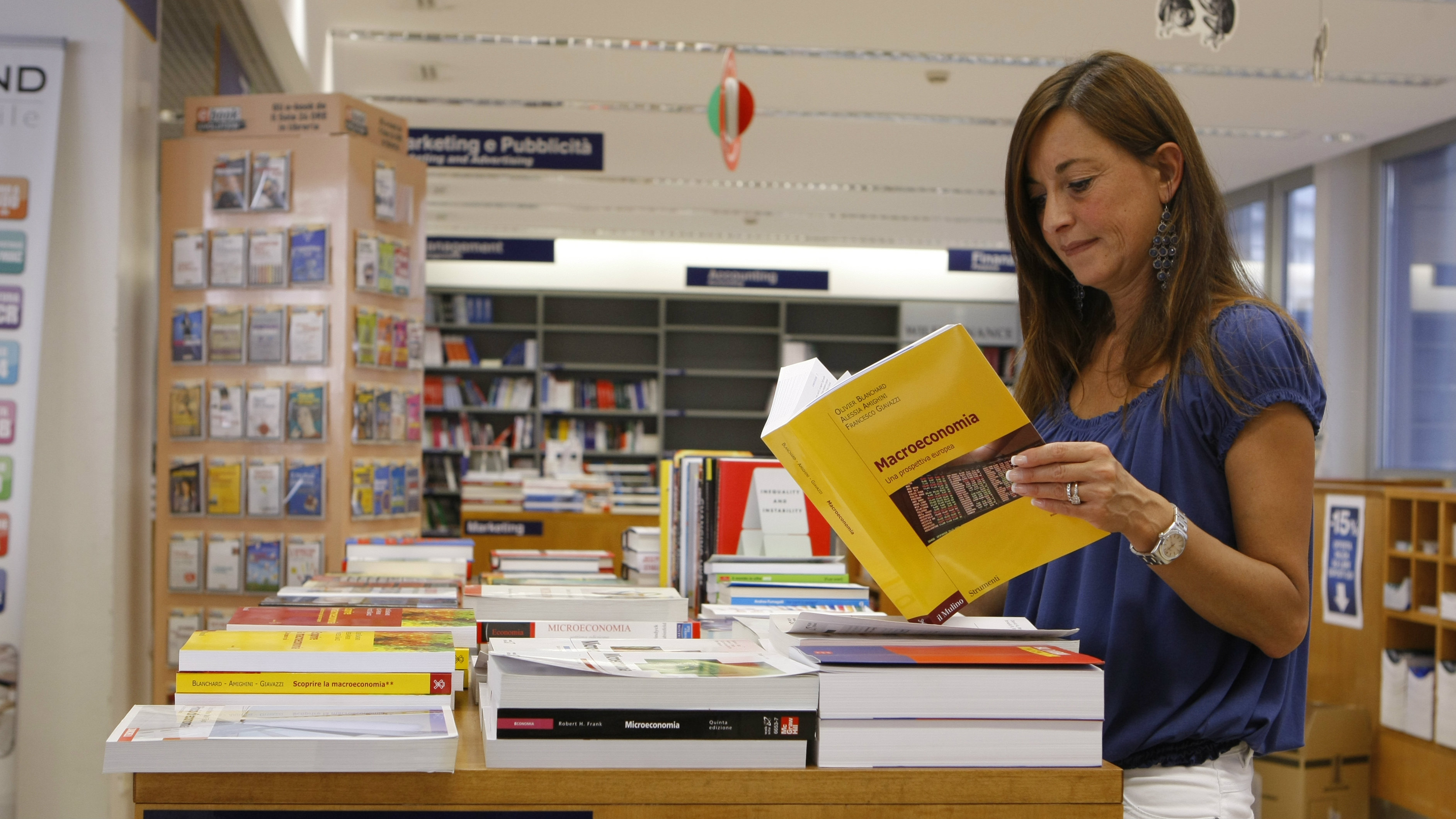 A woman poses with a textbook in the economics section of a book store in