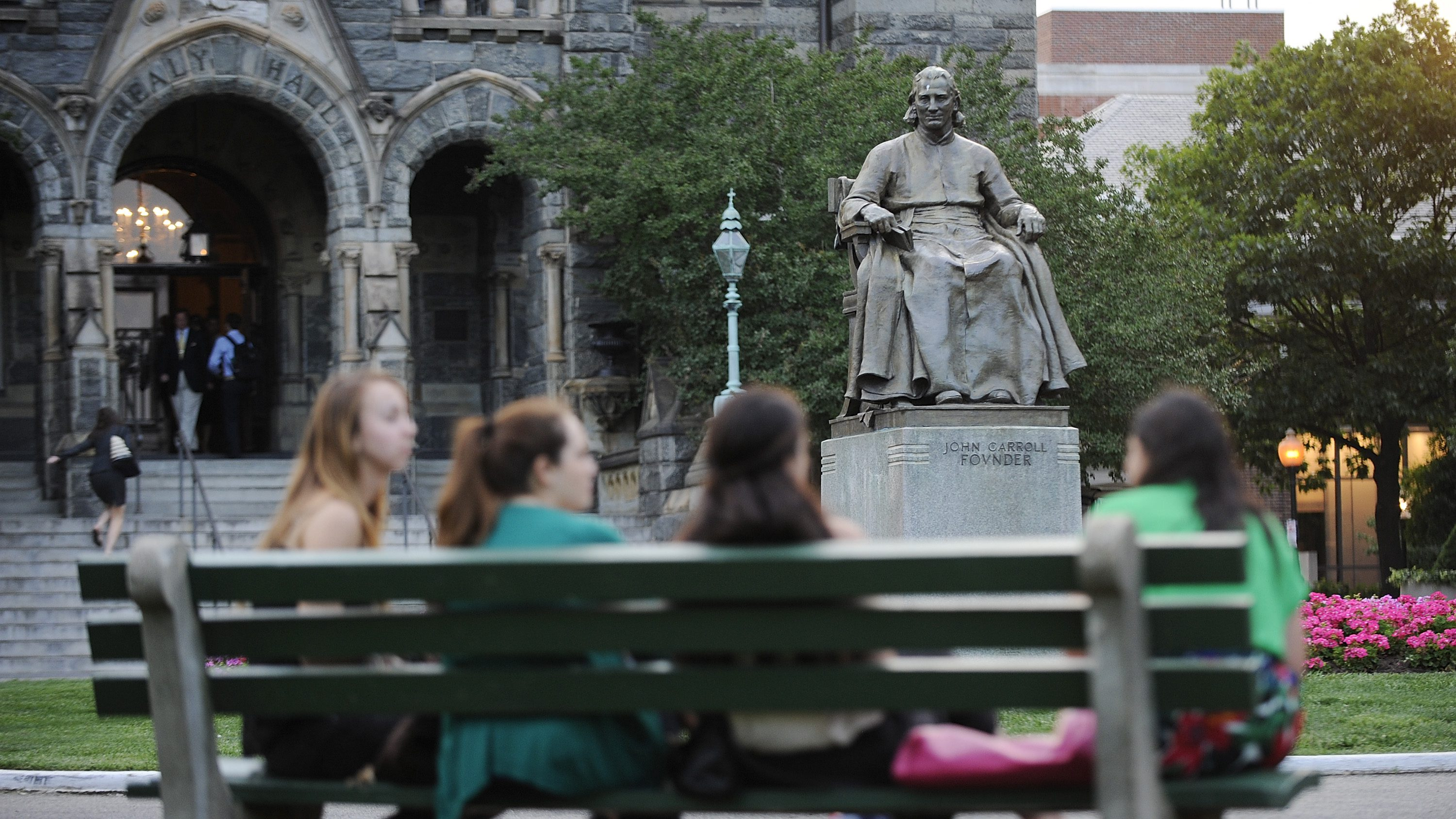 A statue of John Carroll, first Archbishop of Baltimore and founder of Georgetown University, overlooks a group of women seated on a bench on the Georgetown campus in Washington June 14, 2012. New rules requiring free access to prescription birth control for women with health insurance go into effect on August 1, 2012, but controversy lingers at some Catholic institutions struggling to balance the requirement with their opposition to contraception. At Georgetown, the nation's oldest Catholic university, students and administration officials are still wrestling with the requirement to cover contraceptives as part of larger effort to expand no-cost preventive care for women. Picture taken June 14, 2012. REUTERS/Jonathan Ernst    (UNITED STATES - Tags: HEALTH EDUCATION SOCIETY) - RTR35V72