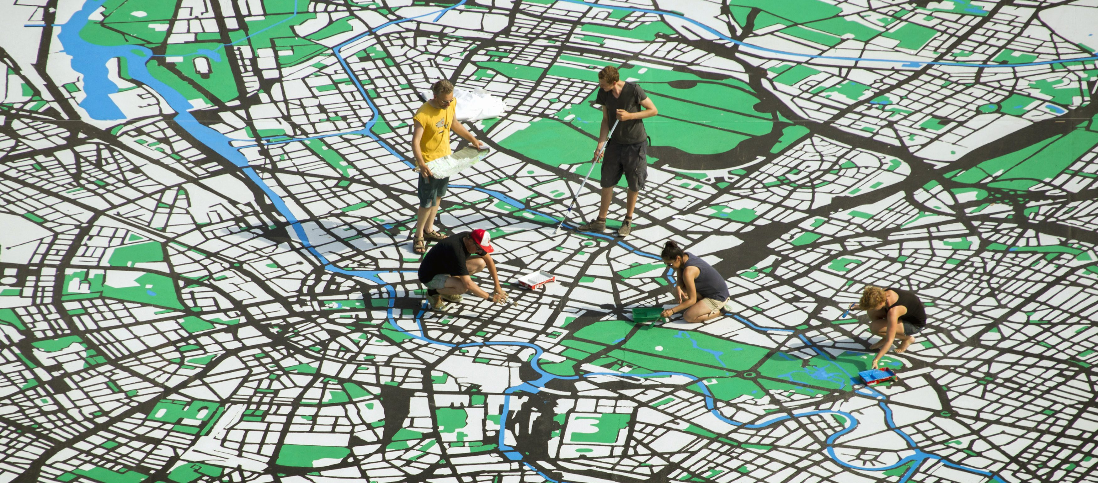 Artists work on a giant city map of Berlin that is drawn on a concrete square in central Berlin
