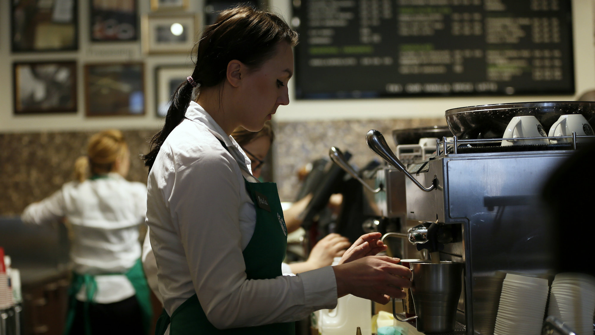 A young barista prepares a drink at a Starbucks.