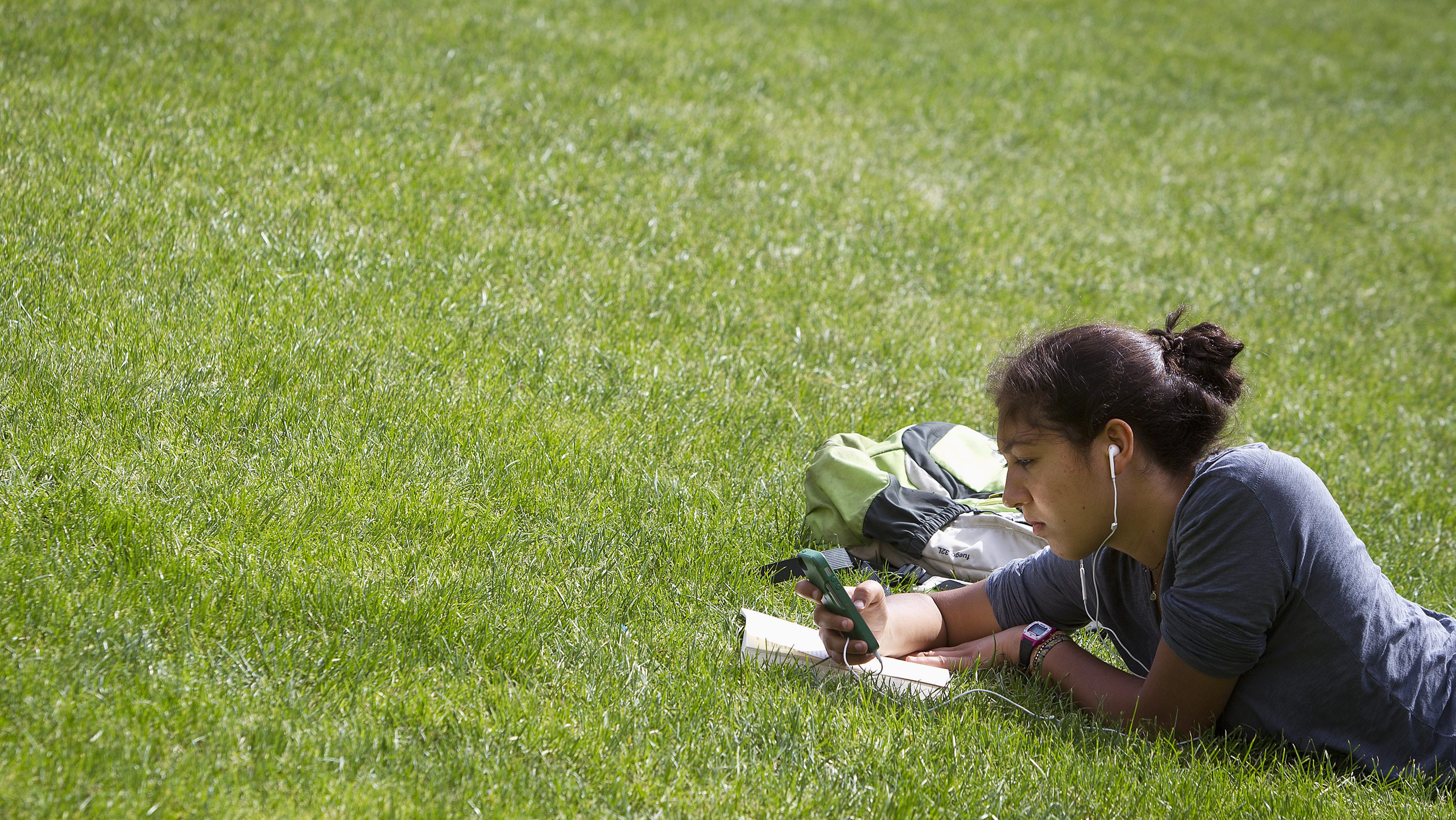 A woman lies in the grass reading a book and listening to music at Columbia University in New York, April 14, 2014. REUTERS/Carlo Allegri (UNITED STATES - Tags: SOCIETY ENVIRONMENT EDUCATION) - RTR3LA5V