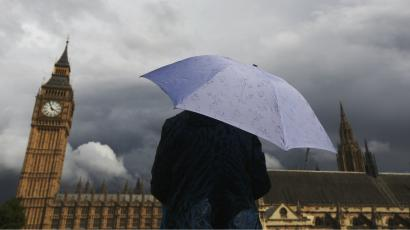 A woman looks towards dark clouds over the Houses of Parliament in central London.