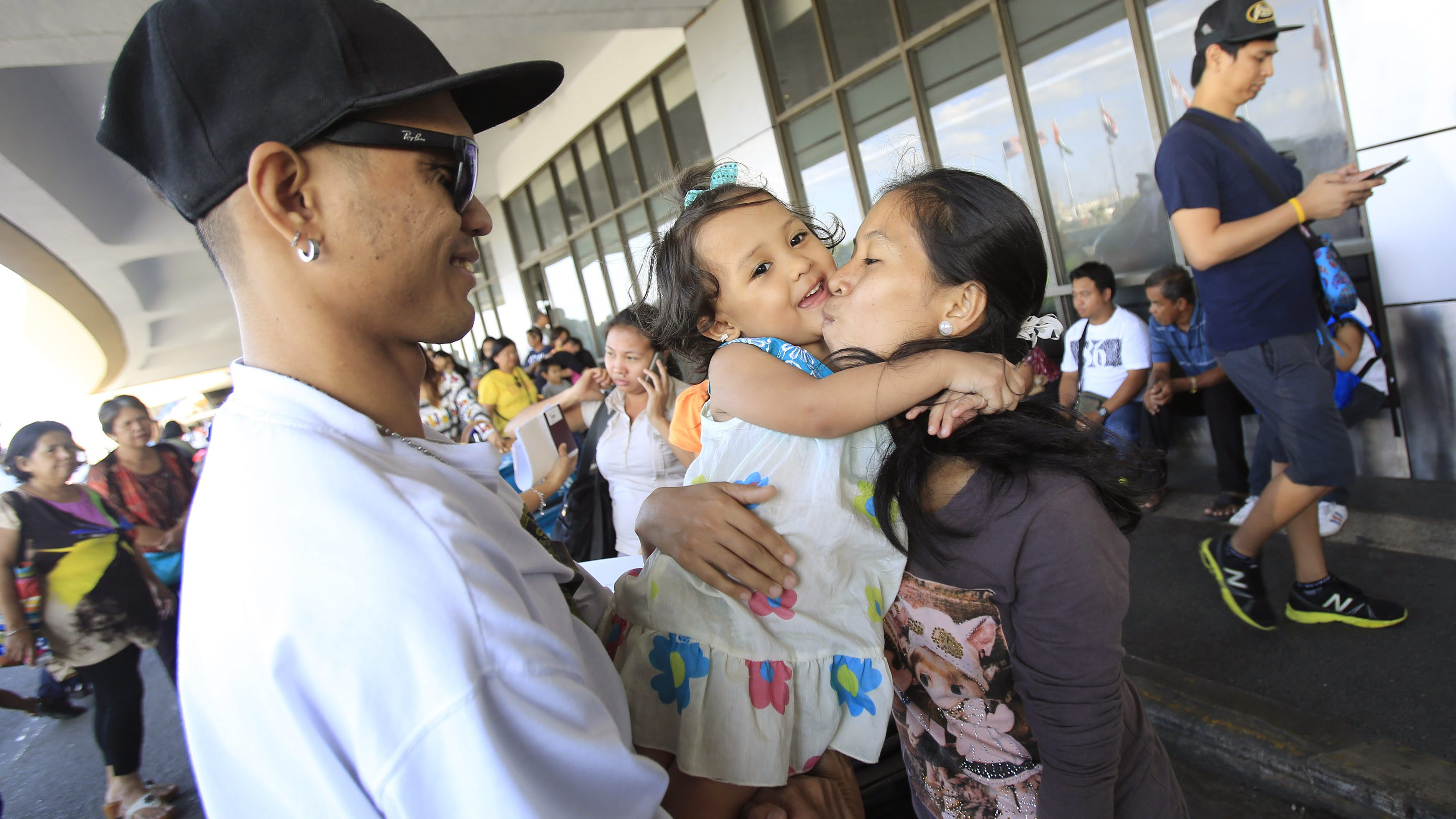 Joan Osillos, an Overseas Filipino Worker (OFW) working in Qatar, hugs and kisses goodbye to her 3-year-old daughter Chelsie, while her husband Mark Anthony looks on before boarding a flight at an international airport in Manila January 12, 2015. Almost 5,000 Filipinos left their homes every day between 2010 and 2013 to seek work overseas, government data shows, most hoping to provide an education for their children and to meet the most basic needs of their families. The strain of decades of labor migration has come with a significant social cost in Asia's largest Catholic community and likely will be addressed by Pope Francis during his first visit to the Philippines on Thursday. Picture taken January 12, 2015.