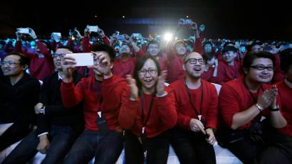 Xiaomi staff and users of Xiaomi phones react at the launch ceremony of the Mi Note in Beijing
