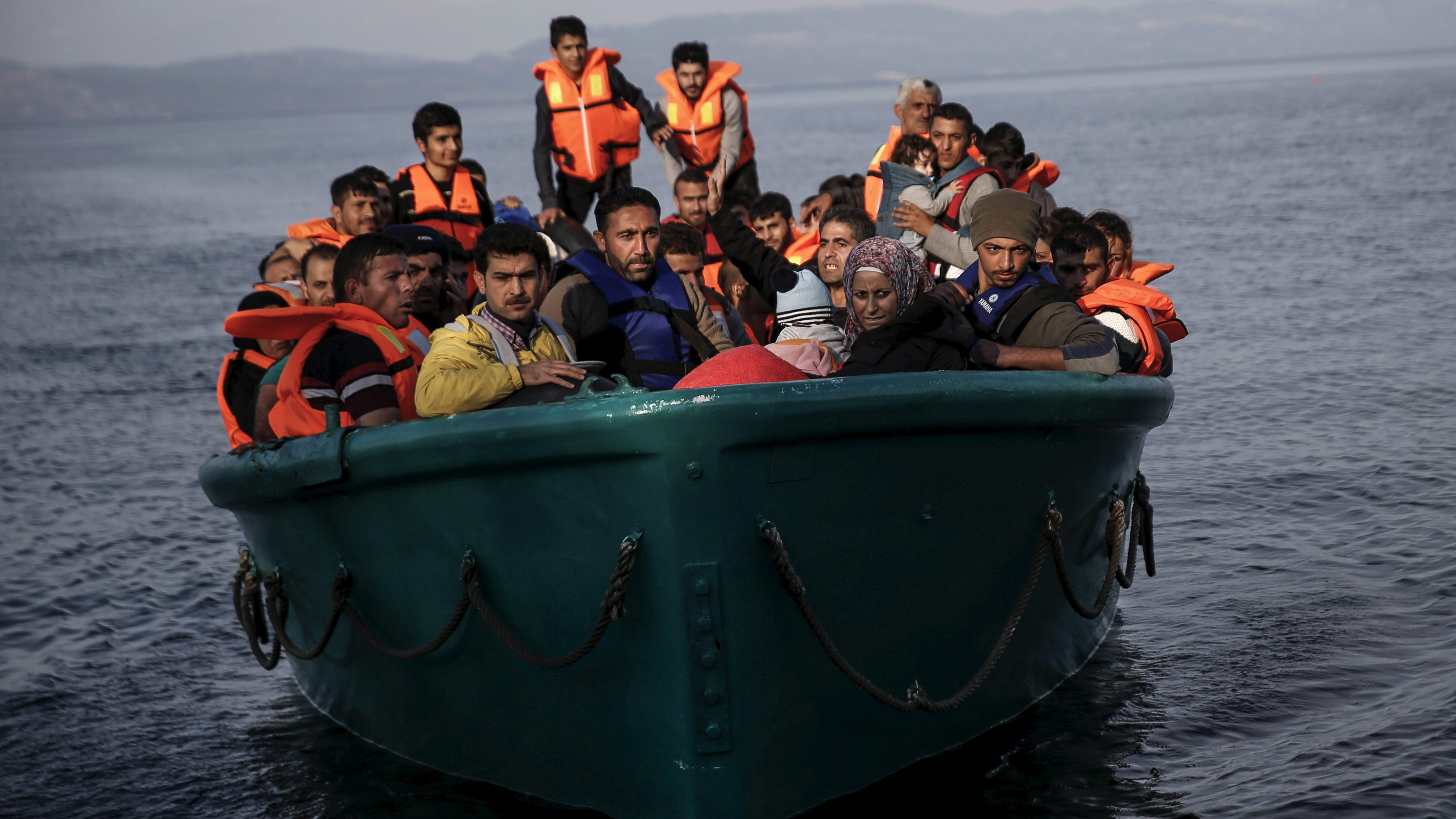 Refugees and migrants arrive on an overcrowded boat on the Greek island of Lesbos